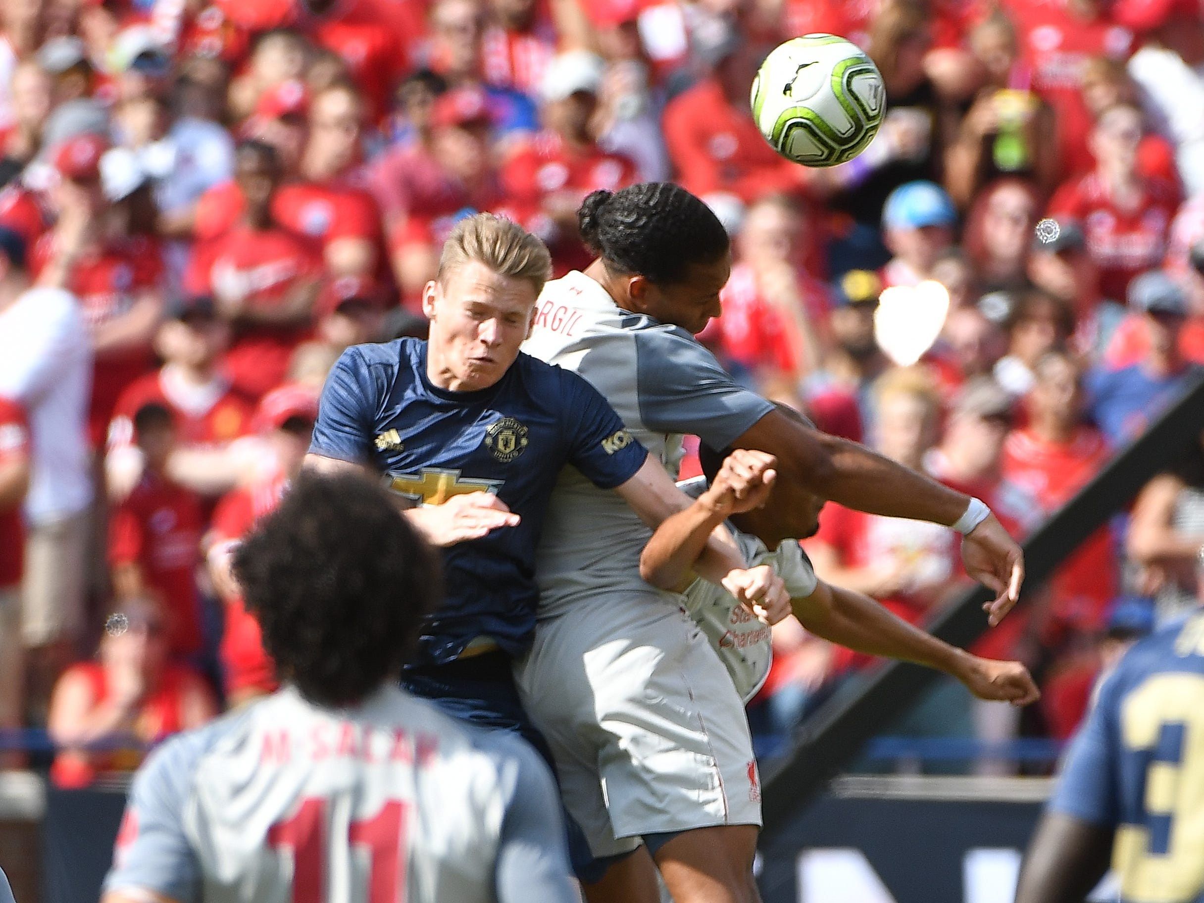Manchester's Scott McTominay goes up for a header against Liverpool's Virgil van Diijk in the first half.