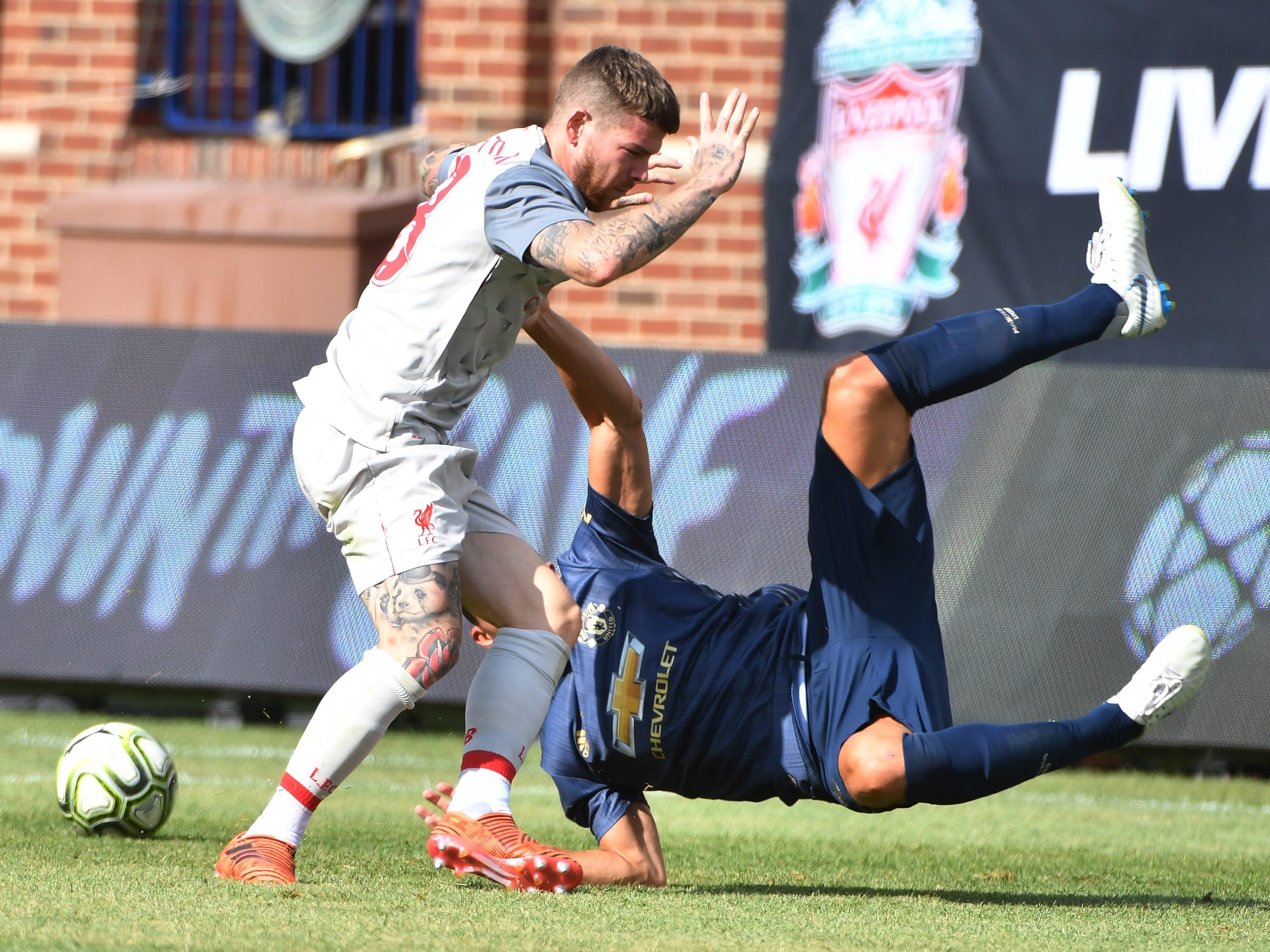 Liverpool's Alberto Moreno takes down Manchester's Matteo Darmian in the first half.