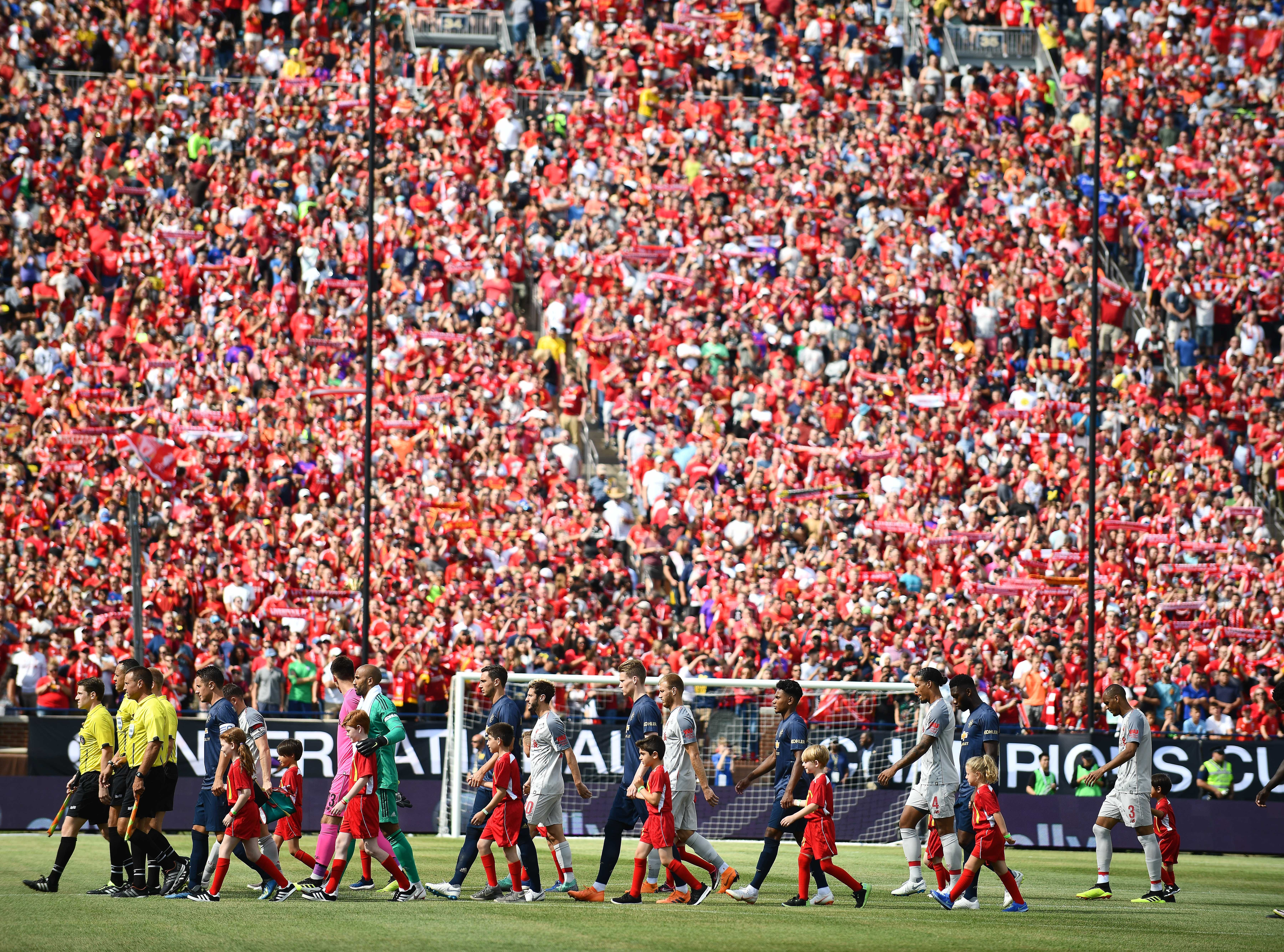 Manchester United and Liverpool make their way onto the field as over 100,000 fans cheer them on at the 'Big House.'