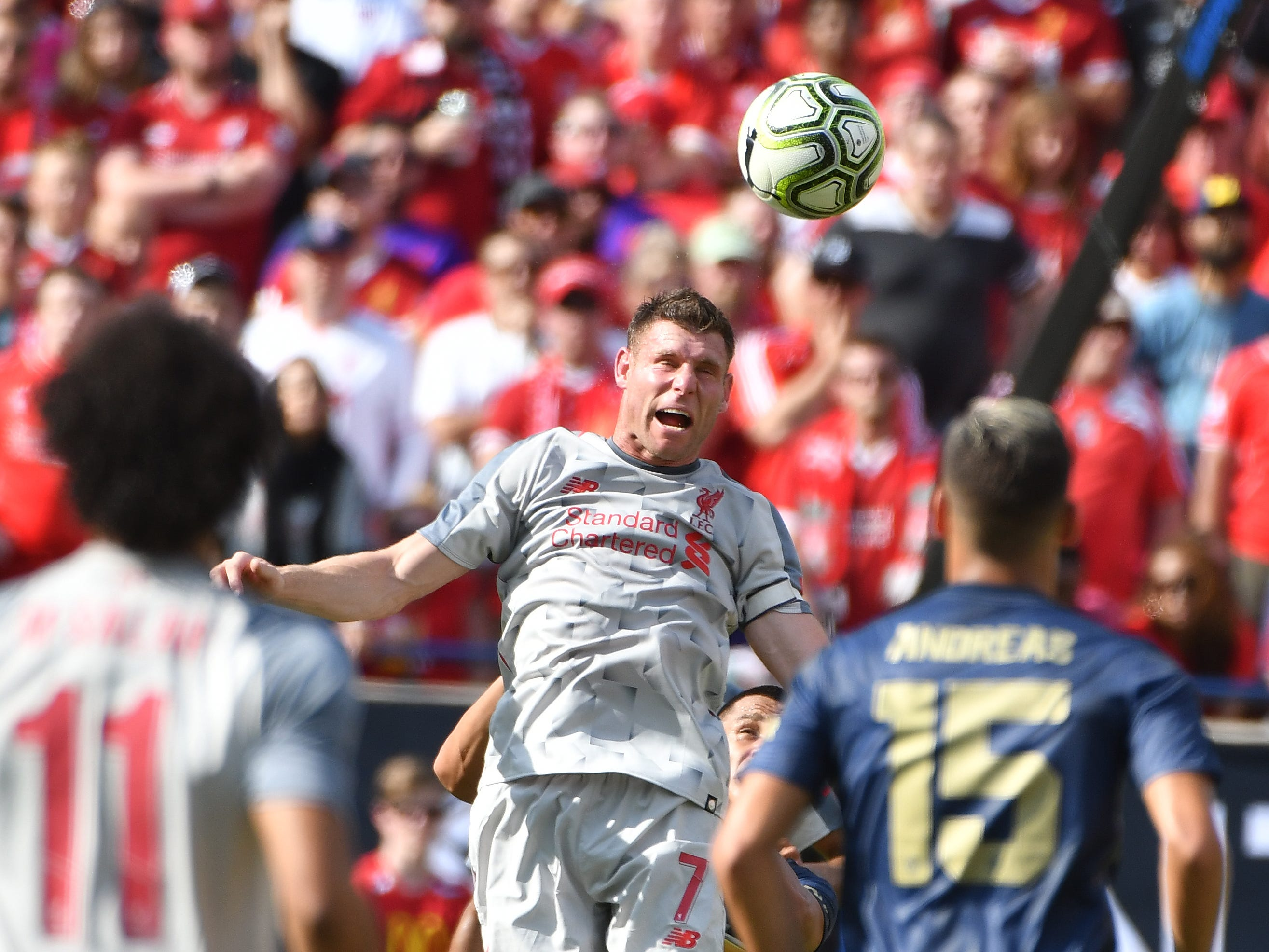Liverpool's James Milner heads a ball bak up field in the first half.