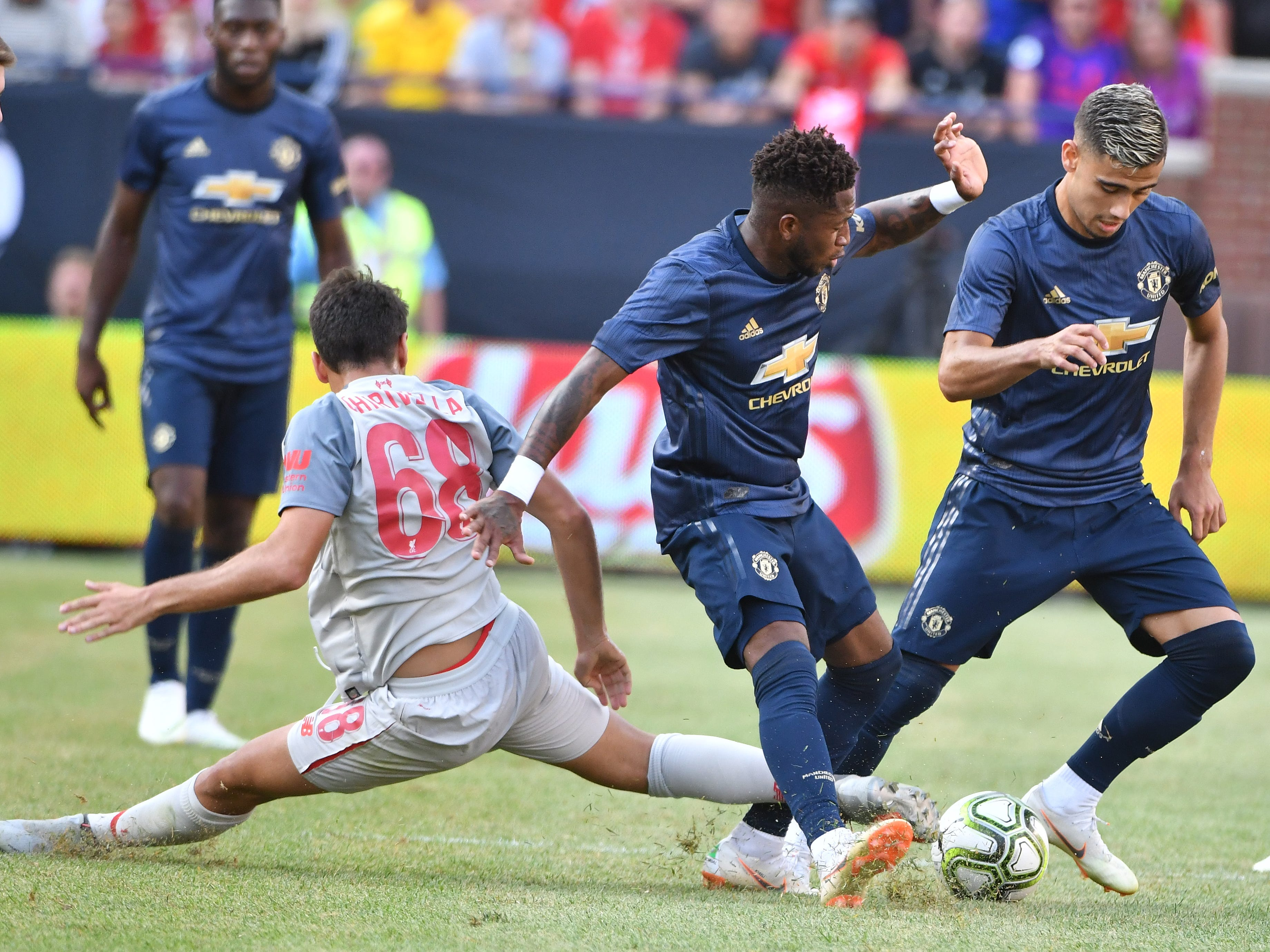 Liverpool's Pedro Chirivella defends against Manchester's Fred and Andreas Pereira in the second half.