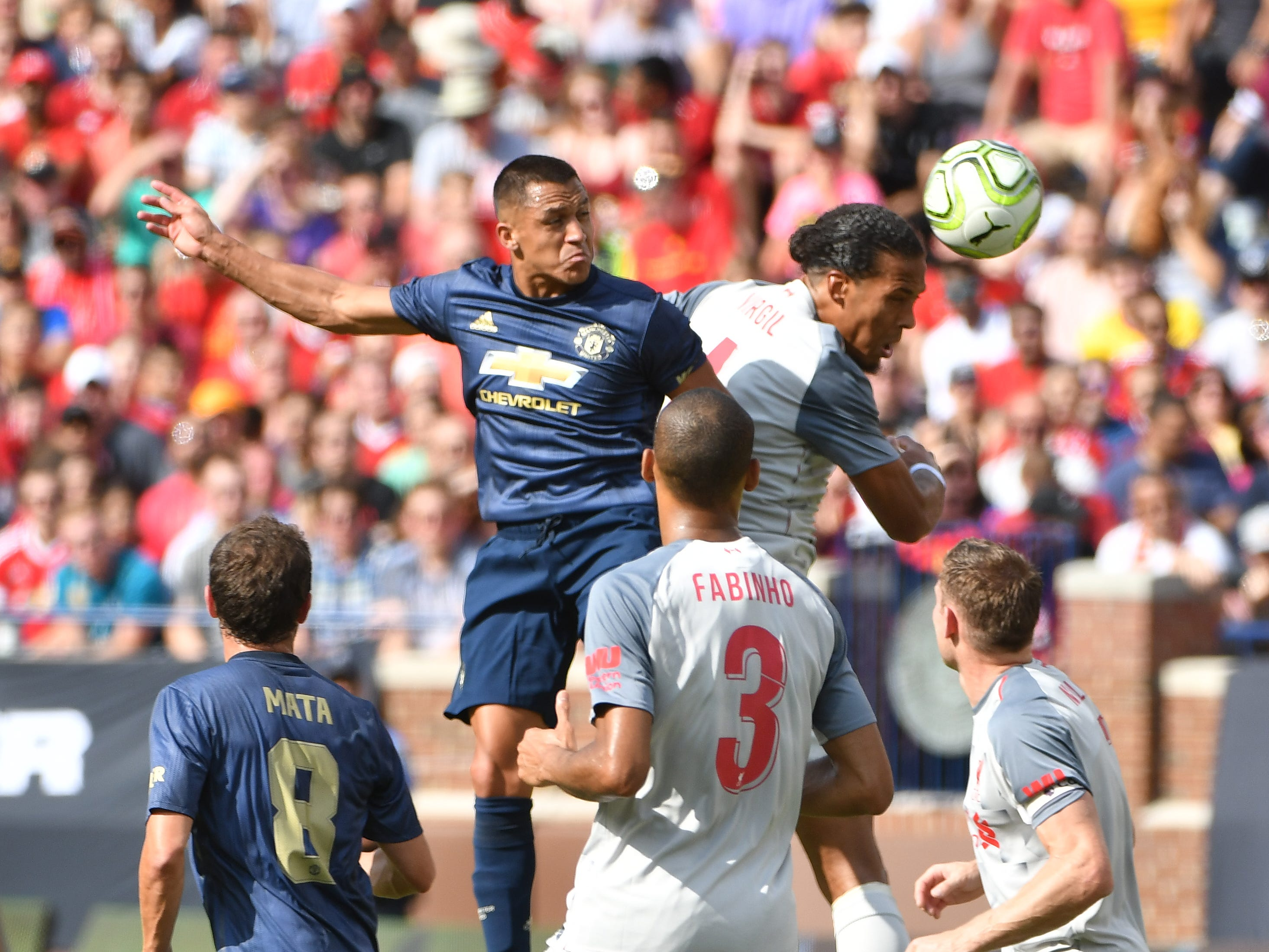 Manchester's Alexis Sanchez and Liverpool's Virgil van Diijk go up for a ball in the first half.