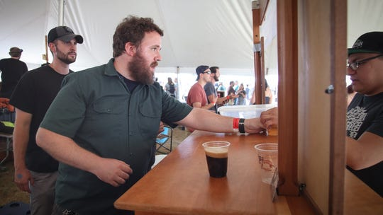 Ryan Walker, head brewer at Fort Street Brewery in Lincoln Park, hands out a beer at the Michigan Brewers Guild Summer Beer Festival in Ypsilanti Saturday.