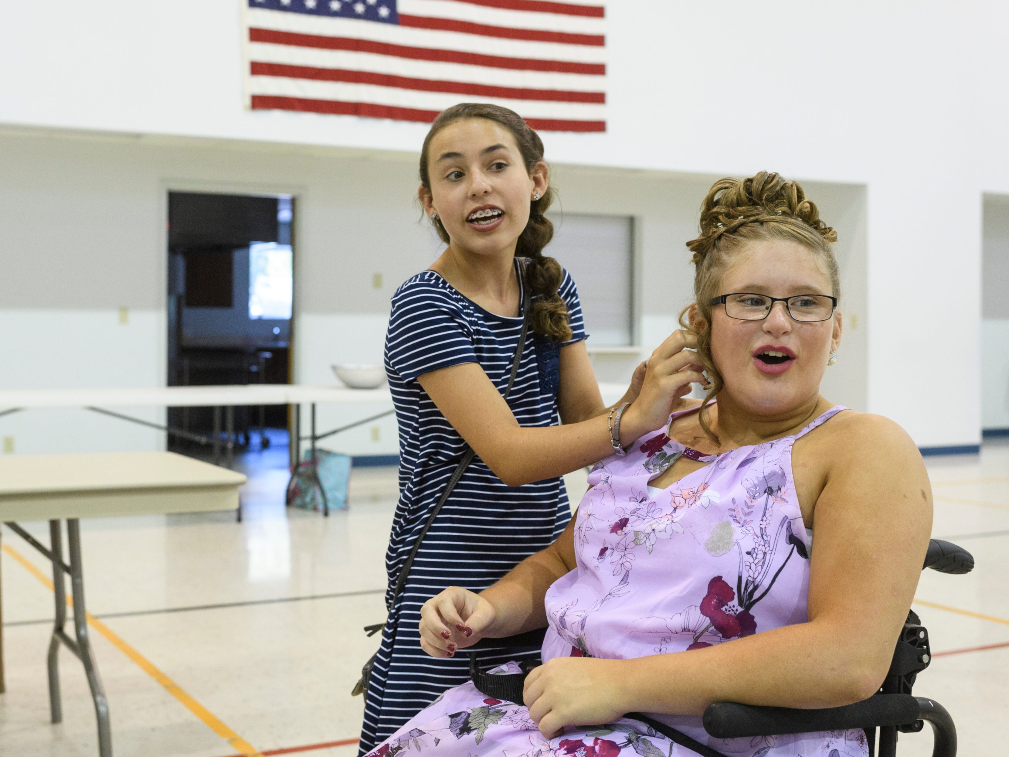 Macie Leeds, 13, helps take off Ali Shanks's interview jewelry as they wait for other contestants to finish their interviews with the pageant judges at the Salem Church of Darmstadt, Saturday afternoon, July 28, 2018. Leeds, who has been friends with Shanks since kindergarten, spent the afternoon helping Shanks prepare for the pageant.
