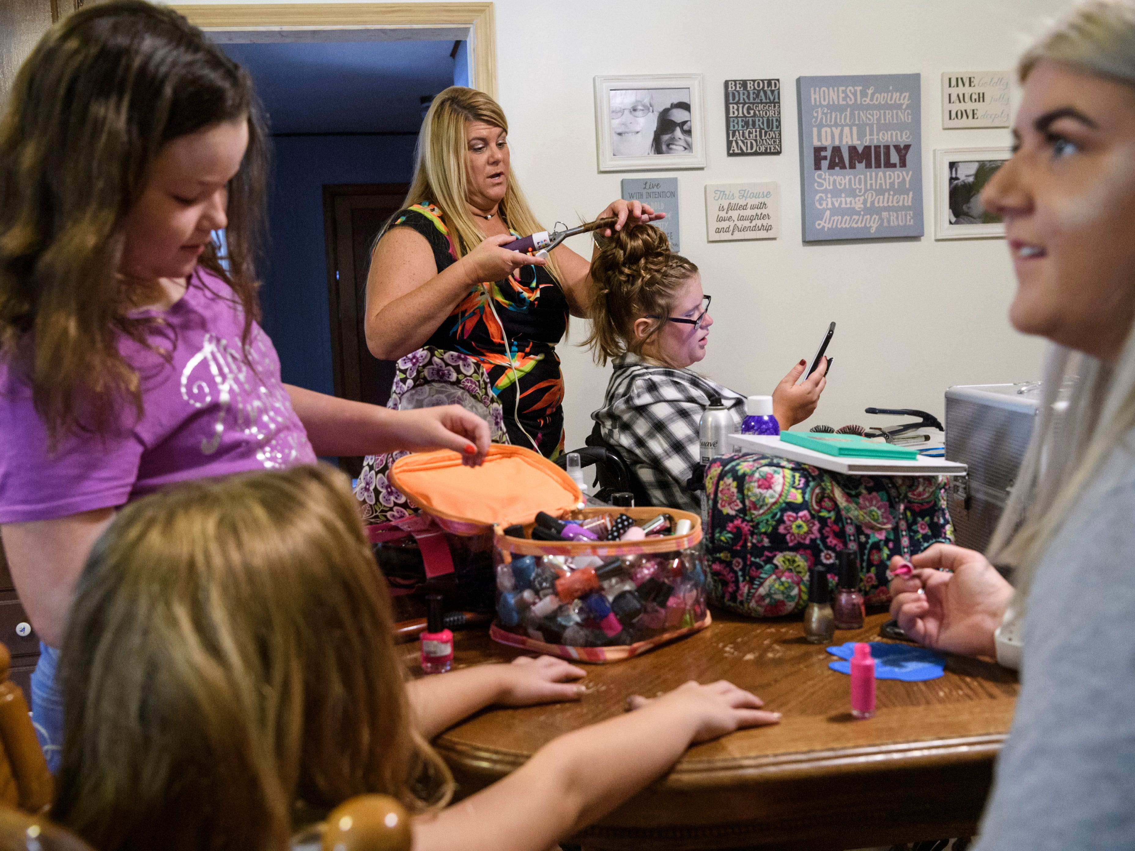 Ali Shanks, back right, receives a fancy updo from her Aunt Shawn O'Nan, back left, as Addison Swanson, front left to right, and Ella Swanson pick out nail polish and make-up for Kylie O'Nan to help them apply to their faces and nails while preparing for the Miss Golden pageant at the Shanks household in Evansville, Saturday morning, July 28, 2018. The kitchen was filled sounds of laughter and pop music as the girls helped Ali get ready for her fourth Miss Golden pageant.