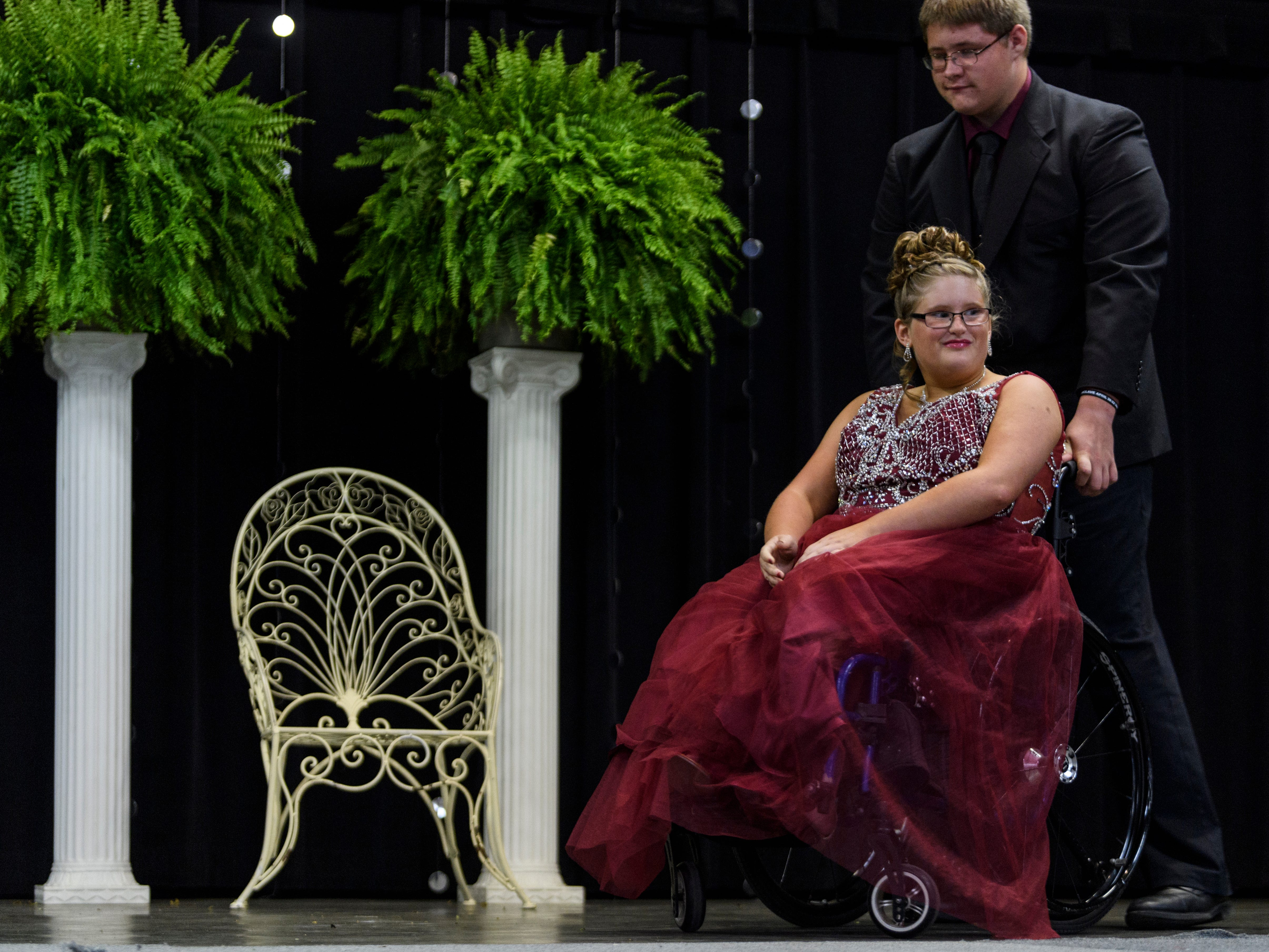 Ali Shanks is wheeled off stage by her escort Lucas Wolf after being introduced to the audience during the 2018 Miss Golden pageant at the Vanderburgh 4-H Center Auditorium in Evansville, Ind., Saturday evening, July 28, 2018.