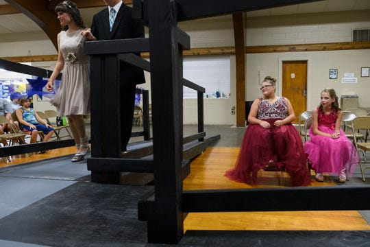 Heather Benford, from left, and her escort Connor Jones walk to the stage as her fellow pageant contestants Ali Shanks and Shelby Buckwinkel wait for their turns during the 2018 Miss Golden pageant at the Vanderburgh 4-H Center Auditorium in Evansville, Ind., Saturday, July 28, 2018. Six girls competed in the fourth annual pageant, which is held for girls with special needs on the last night of the Vanderburgh County Fair.