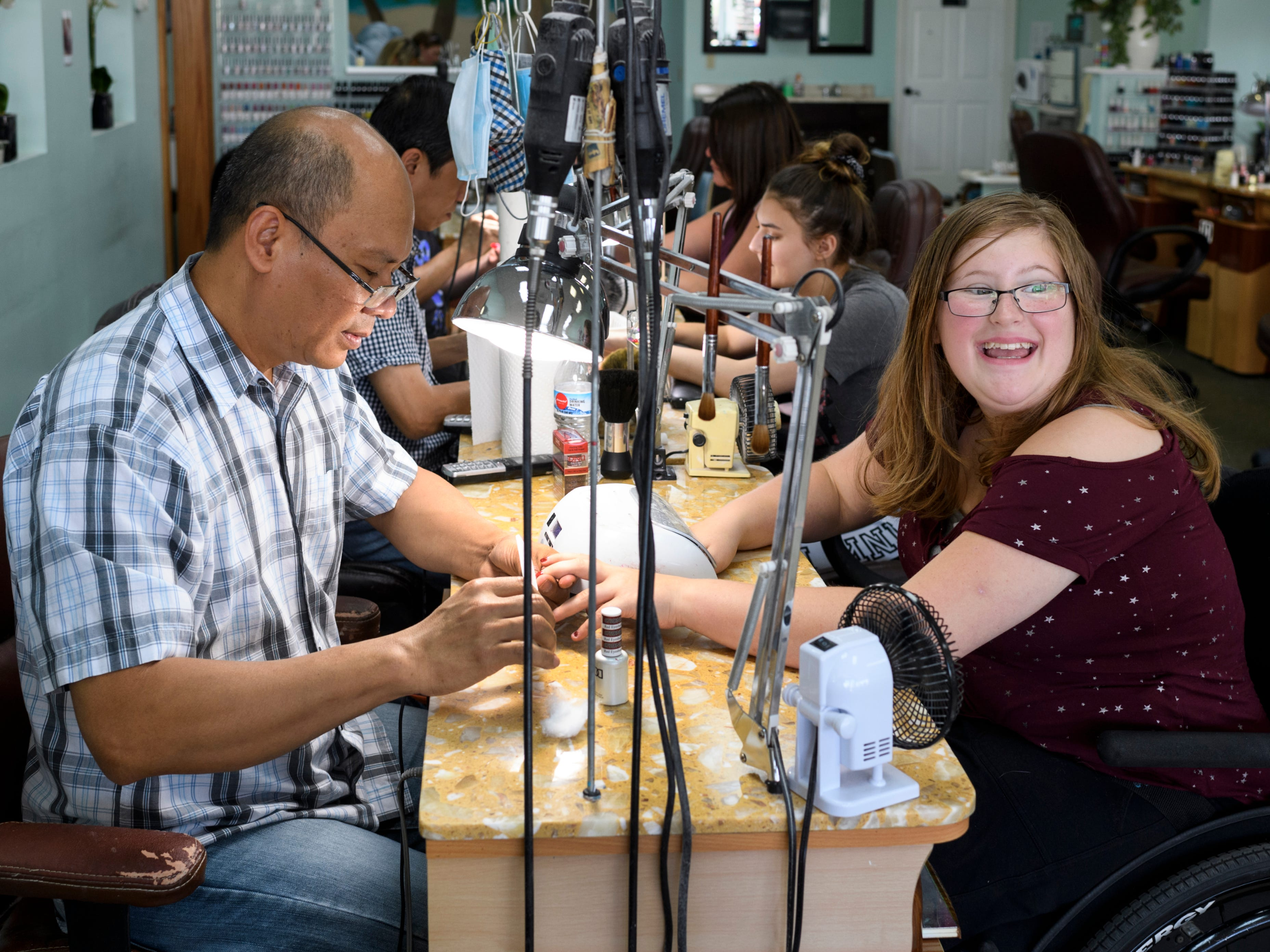 """They look so pretty,"" Ali Shanks, right, says excitedly to her mother Peggy Shanks, not pictured, as she receives a sparkly red manicure from Nail Tech Tony Pham, left, at Lovely Nails on the west side of Evansville, Ind., Wednesday, July 25, 2018. Peggy has been a customer of Pham's for several years and offered to do Ali's nails for free."