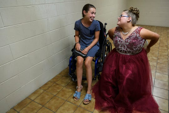 Ali Shanks, right, takes a moment to laugh with her best friend Macie Leeds, left, before being put back in her wheelchair for the start of the 2018 Miss Golden pageant at the Vanderburgh 4-H Center Auditorium in Evansville, Ind., Saturday, July 28, 2018. After spending the afternoon with Shanks, Leeds and her family watched her compete in the pageant.