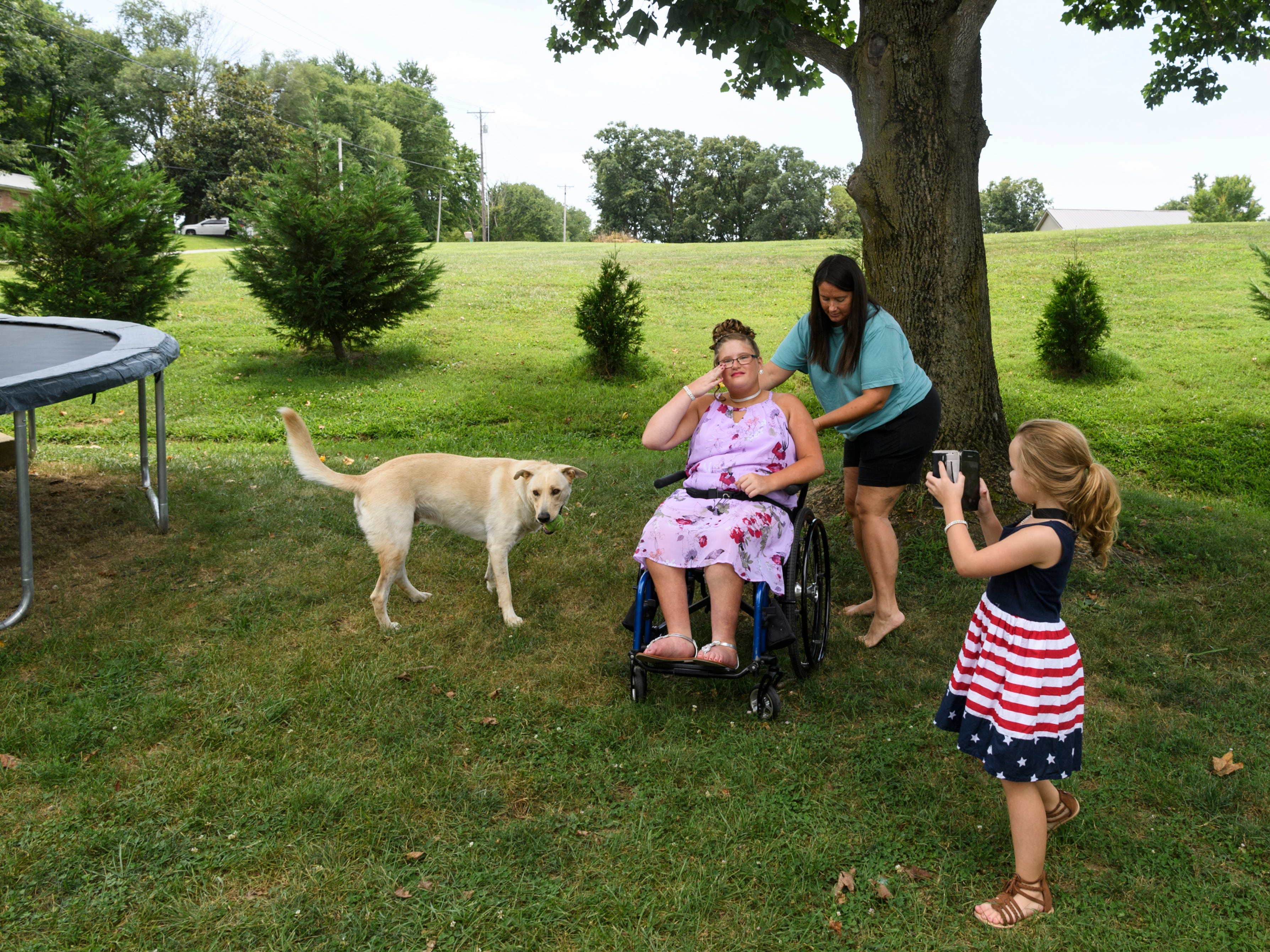 Peggy Shanks positions her daughter Ali Shanks under a shady tree in their yard before taking pictures of her as six-year-old Ella Swanson begins snapping cell phone photos of Ali and Jax, the dog, at their home on the west side of Evansville, Ind., Saturday afternoon, July 28, 2018. Everyone took pictures of Ali in her interview dress before Ali and Peggy headed to the Salem Church of Darmstadt for her pageant interview.