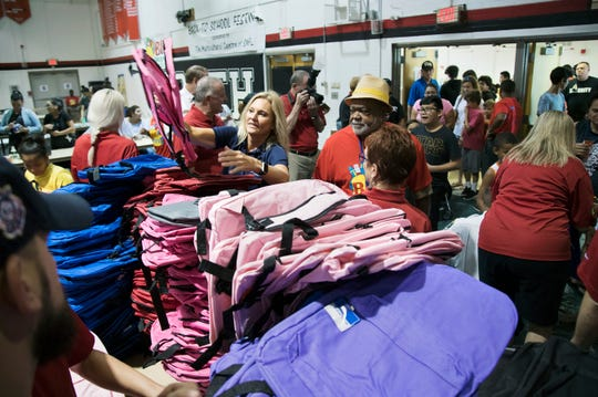 Rep. Heather Fitzenhagen, center, helps pass out school supplies on Sunday at the Big Backpack Event at North Fort Myers High School. More than a 1,000 Lee County students received supplies.