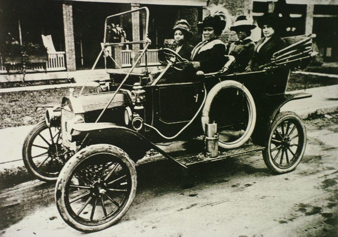 Madam C.J. Walker (1867-1919) is seen at the wheel of an automobile in this photo.
