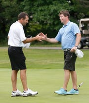 Matt Toney, left, and Ben Mattingly shake hands after Mattingly defeated Toney 4 and 3 to win the Men's City golf championship Sunday, July 29, 2018, on Purdue's Kampen Course.