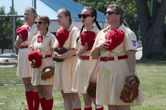 Members of the Rockford Peaches stand for the National Anthem.