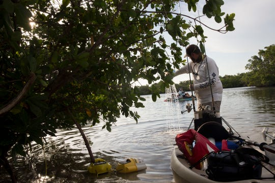 James Smith prepares to put fresh bait in a bucket before setting out on his kayak at Lovers Key State Park during the Heroes on the Water event on Sunday, July 29, 2018.