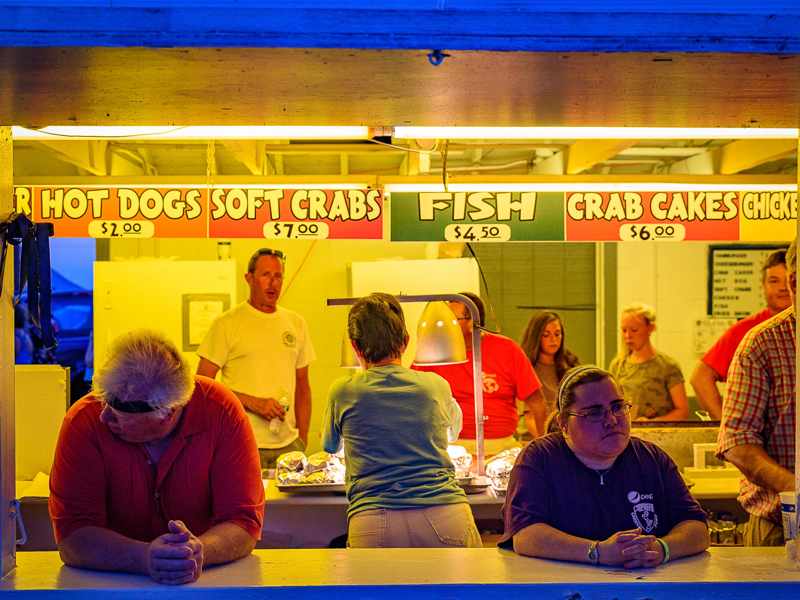 Volunteers wait at one of the many booths serving food at the Chincoteague Fireman's Carnival.