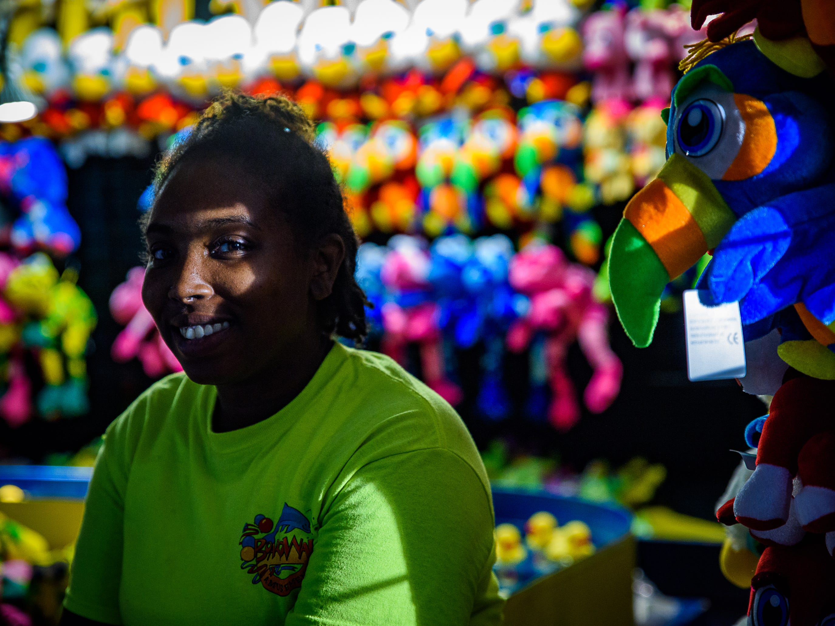 A volunteer stands in front of a wall of prizes at one of the several game booths at the Chincoteague Fireman's Carnival.