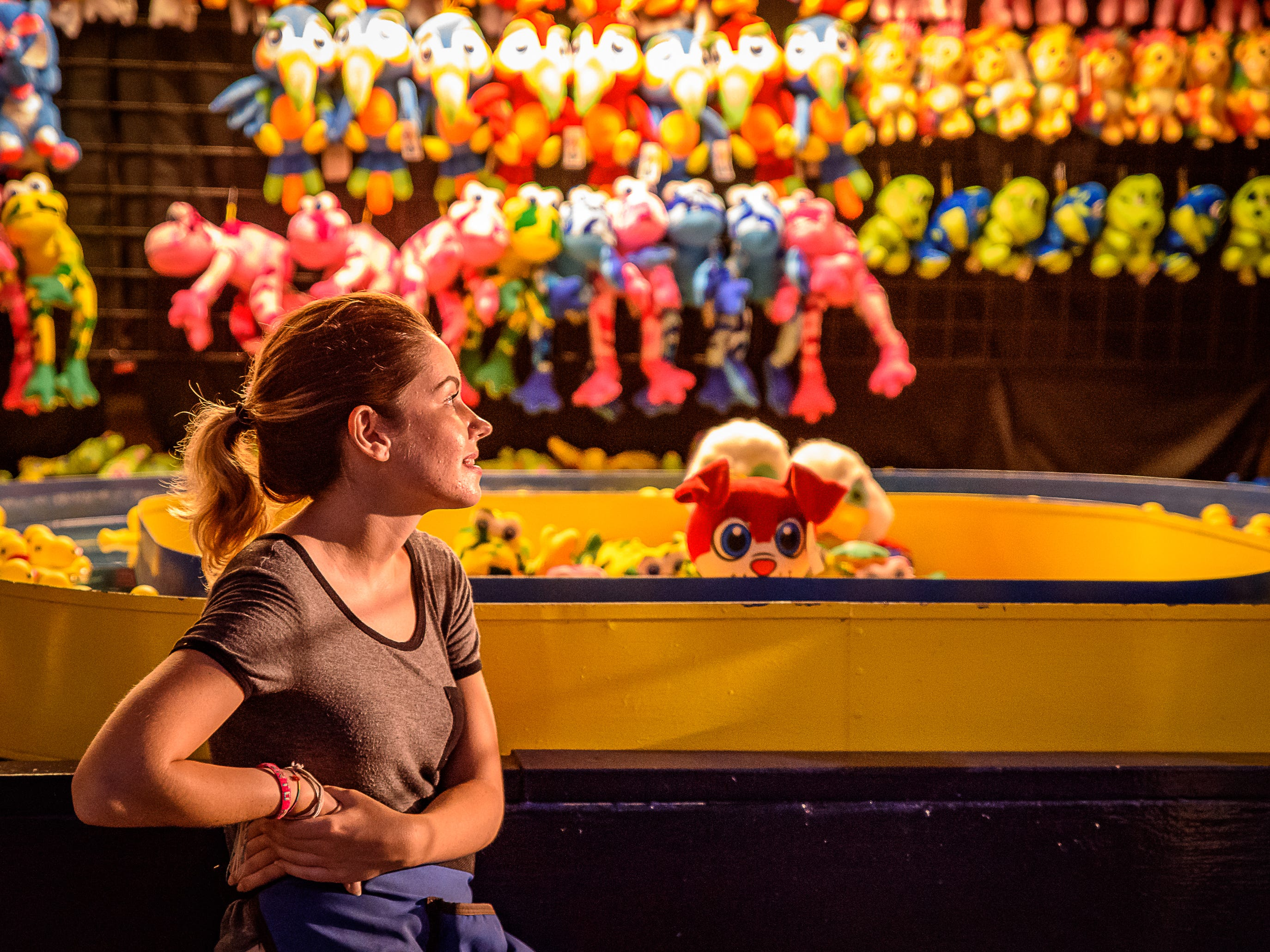 A young volunteer, waits for customers at her game booth at the Chincoteague Fireman's Carnival.