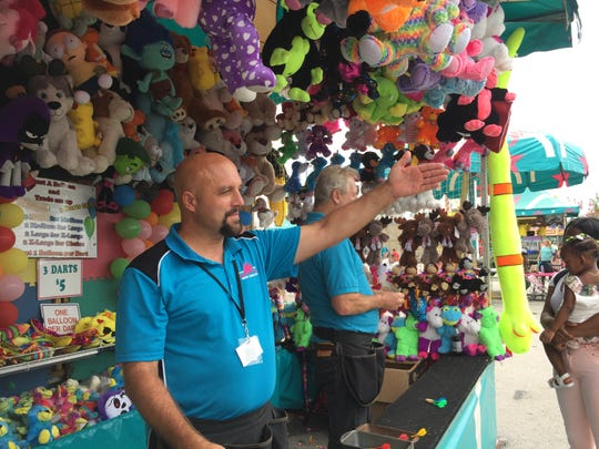 "Jim Jorgensen motions to a passerby to come play the ""pop the balloon"" game at the Ozark Empire Fair."