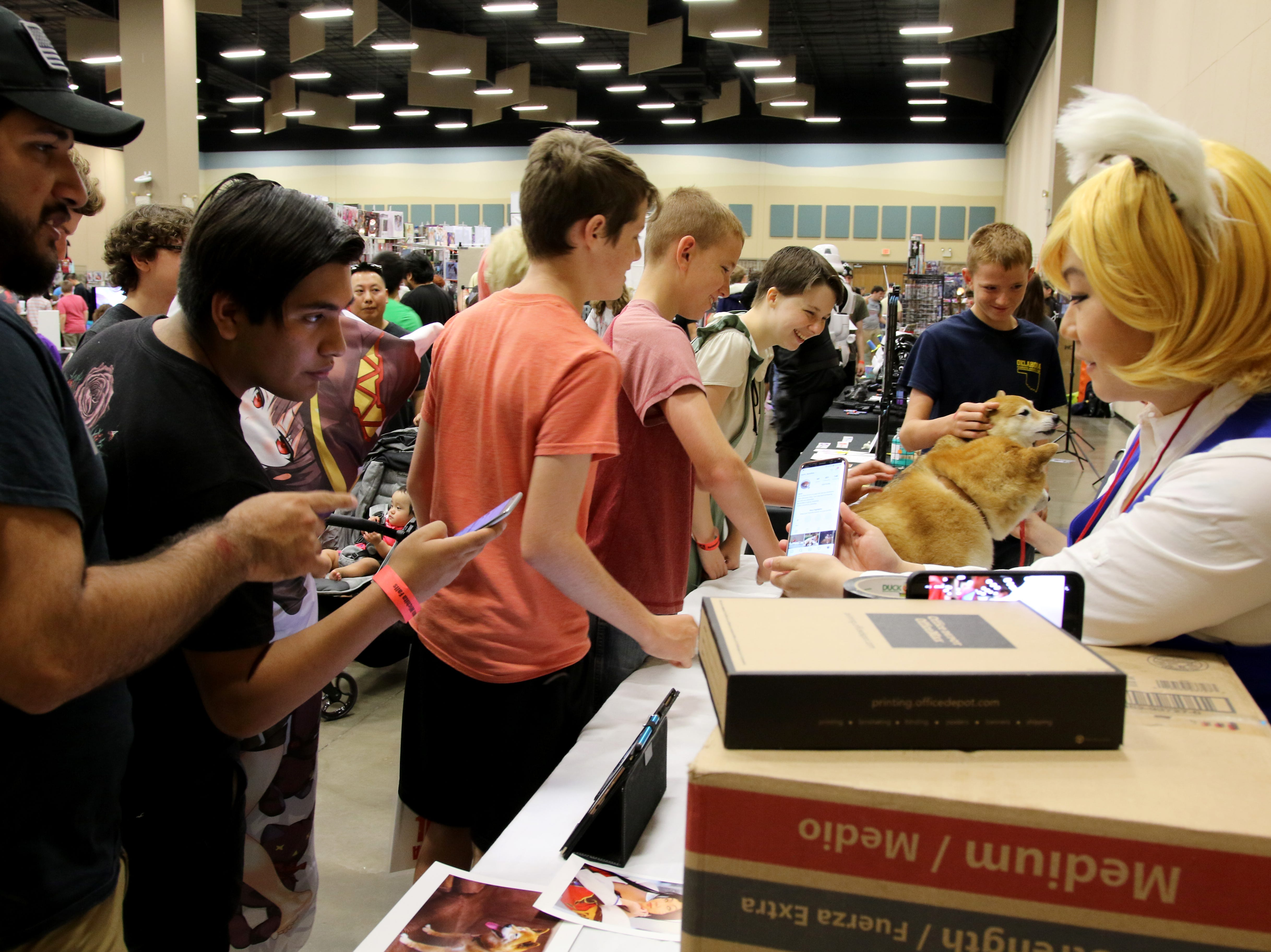 People stand in line to pet dogs at a booth at Animania Saturday, July 28, 2018, in the MPEC Ray Clymer Exhibit Hall.