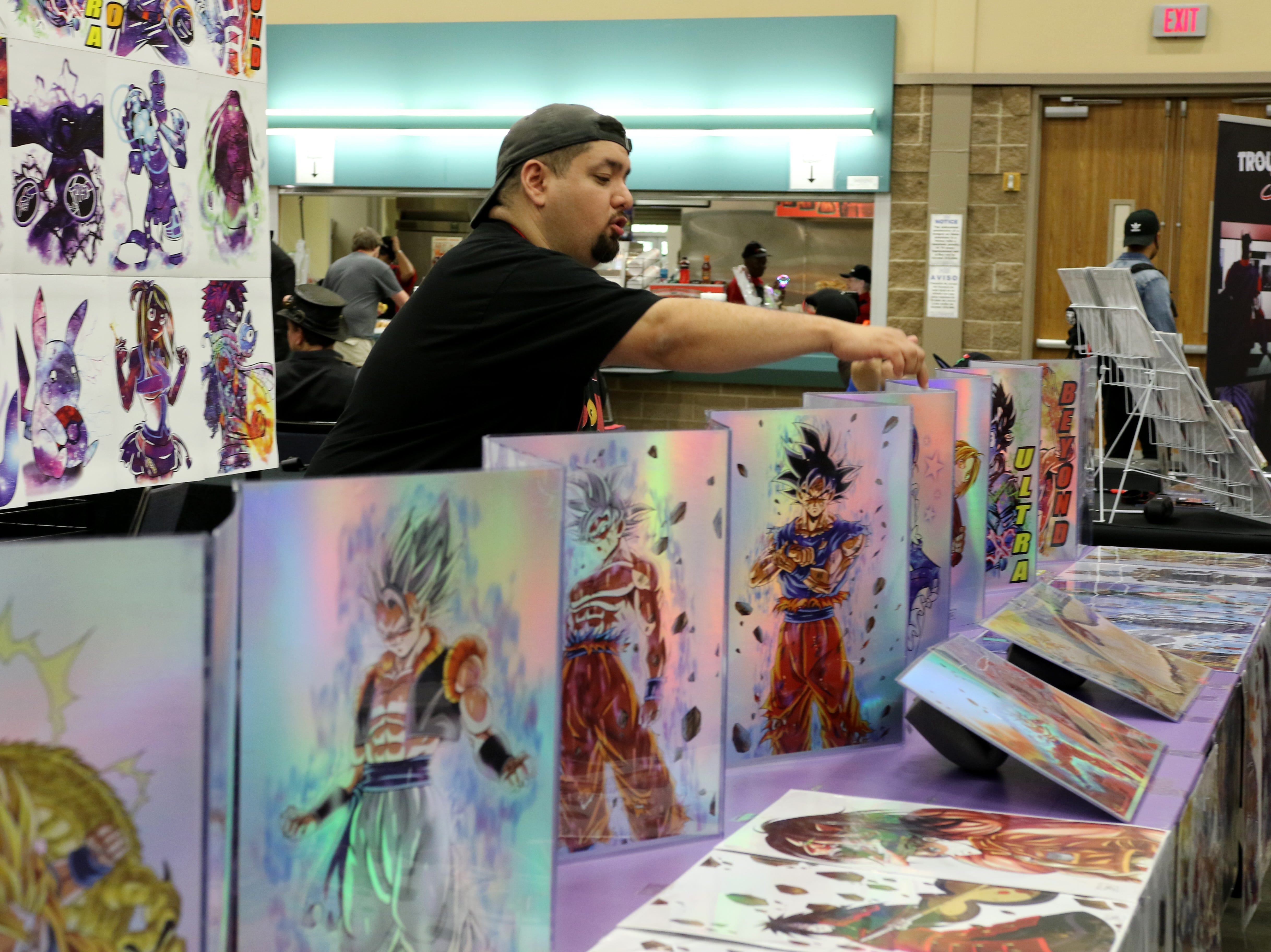 Hector Gutierrez, a representitive of TG Comics sells artwork to Animania attendees  Saturday, July 28, 2018, in the MPEC Ray Clymer Exhibit Hall.