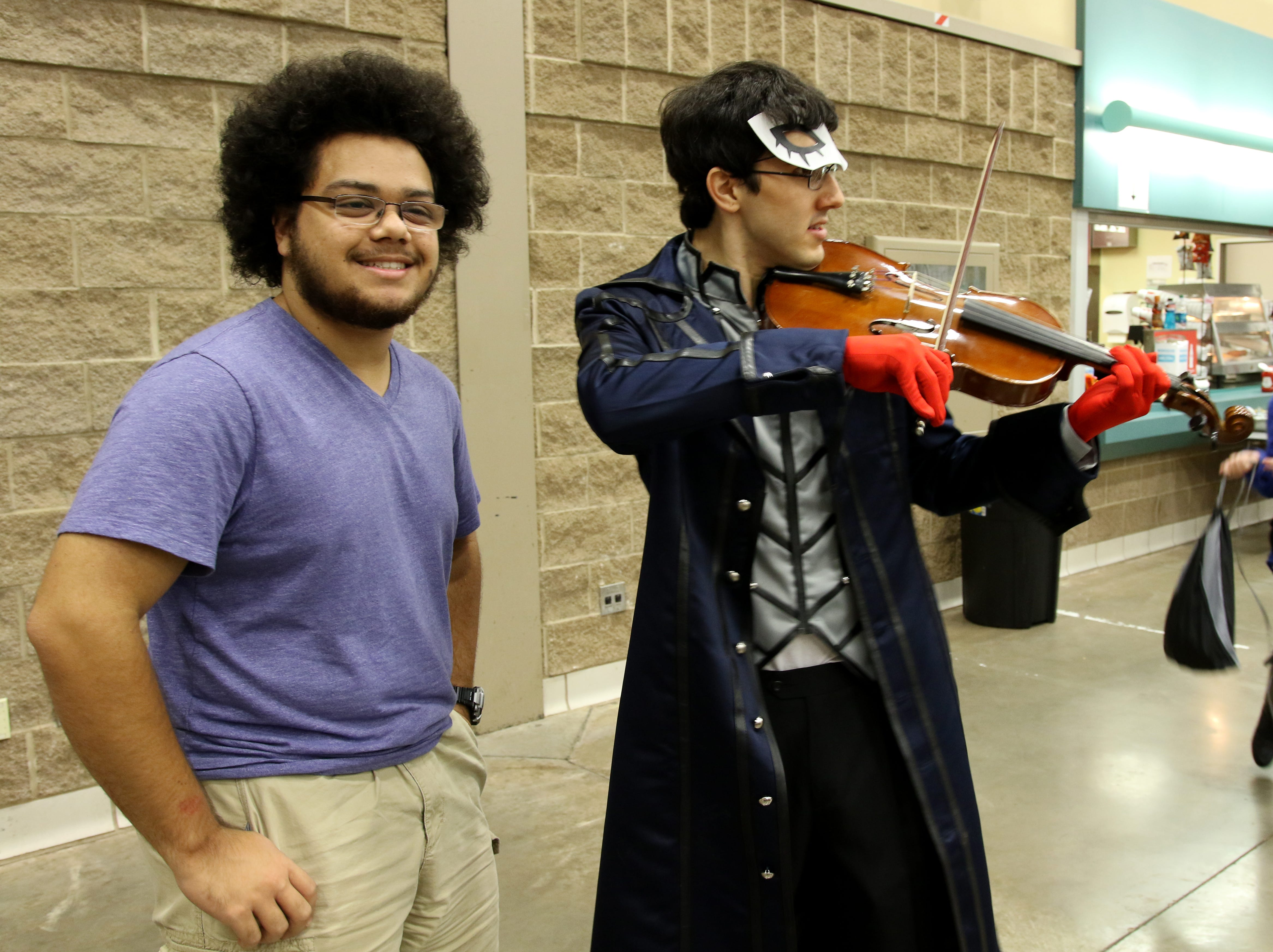 Aaron Hendri has his photo taken with Julian Mendoza, cosplaying as Joker from Persona 5, at Animania Saturday, July 28, 2018, in the MPEC Ray Clymer Exhibit Hall.