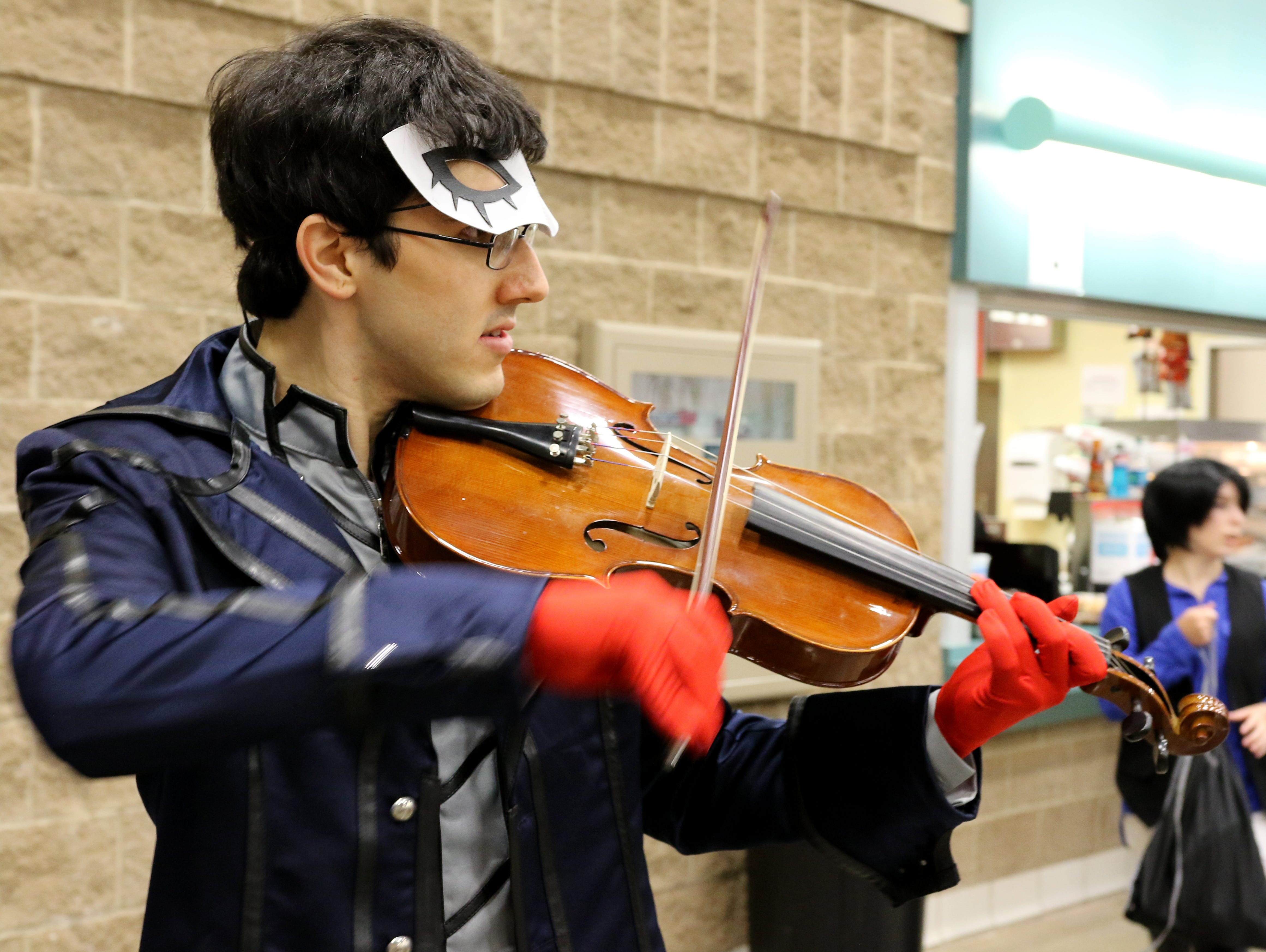 Julian Mendoza, cosplaying as Joker from Persona 5, plays his viola at Animania Saturday, July 28, 2018, in the MPEC Ray Clymer Exhibit Hall.