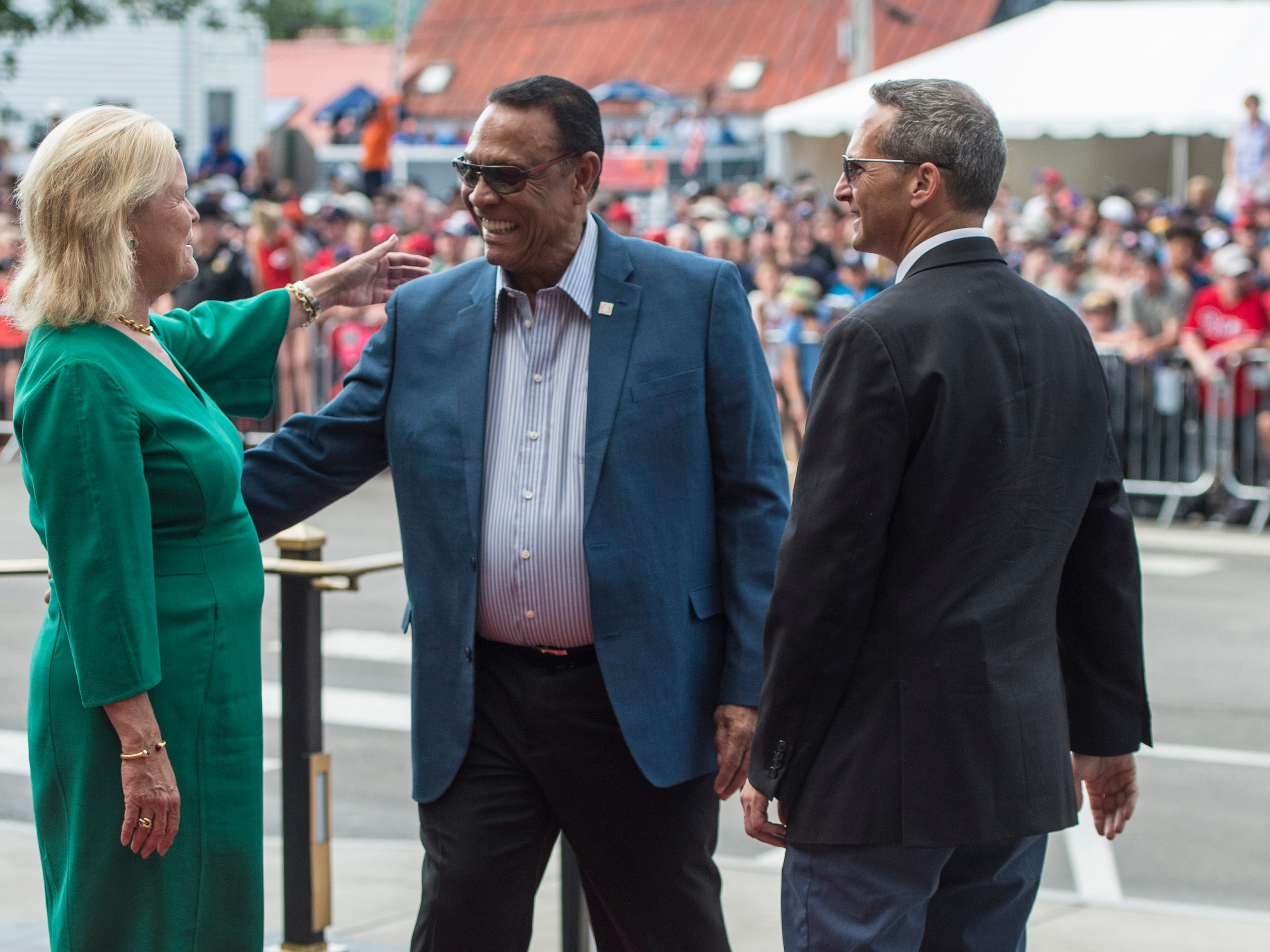 Hall of Fame member Tony Perez (middle) arrives at National Baseball Hall of Fame and is greeted by National baseball Hall of Fame chairman of the board Jane Forbes Clark (left) and Hall of Fame President Jeff Idelson.