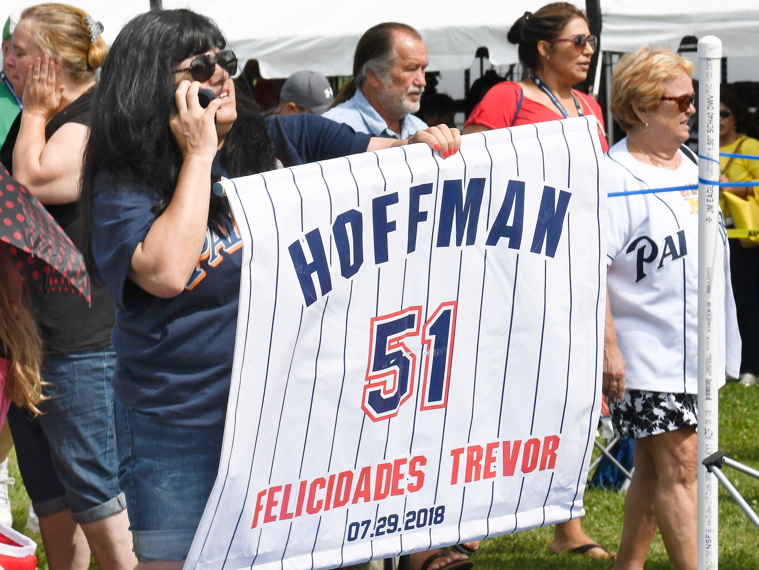 Trevor Hoffman fan Rocio Hodges, of Chula Vista, Calif., uses a banner to find her husband before the start of National Baseball Hall of Fame induction ceremonies.