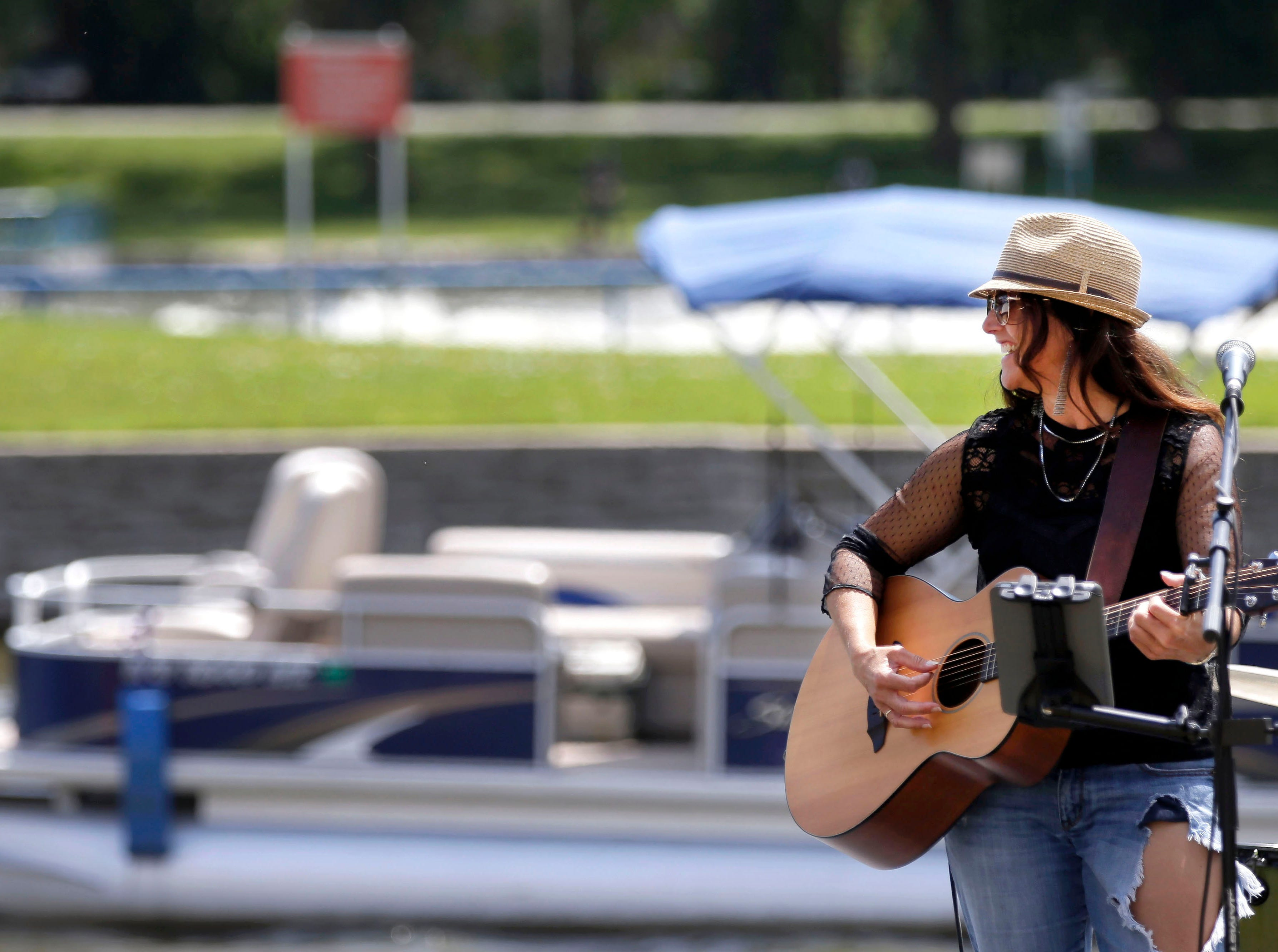 A pontoon passes behind Jodi Gaines as she does a sound check before performing during the Midwest Sunsplash Music Festival Saturday, July 28, 2018, in downtown Menasha, Wis. This year the festival raised funds for Youth Go.Ron Page/USA TODAY NETWORK-Wisconsin