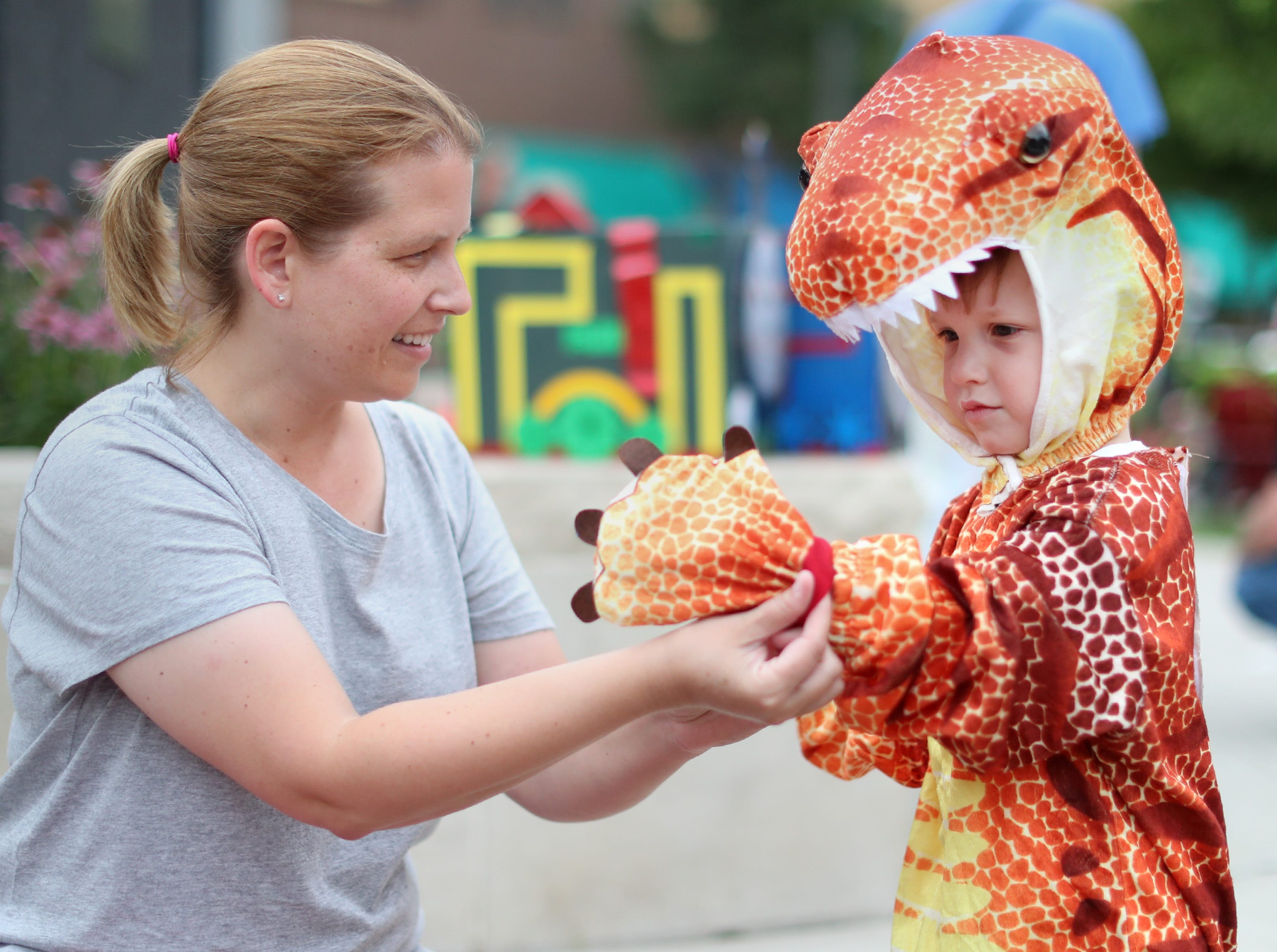 Mara Hendrickson helps her son Max, 3, put on his dinosaur glove during the 10th annual ChildrenÕs Parade Wednesday, July 25, 2018, in Appleton, Wis. Danny Damiani/USA TODAY NETWORK-Wisconsin
