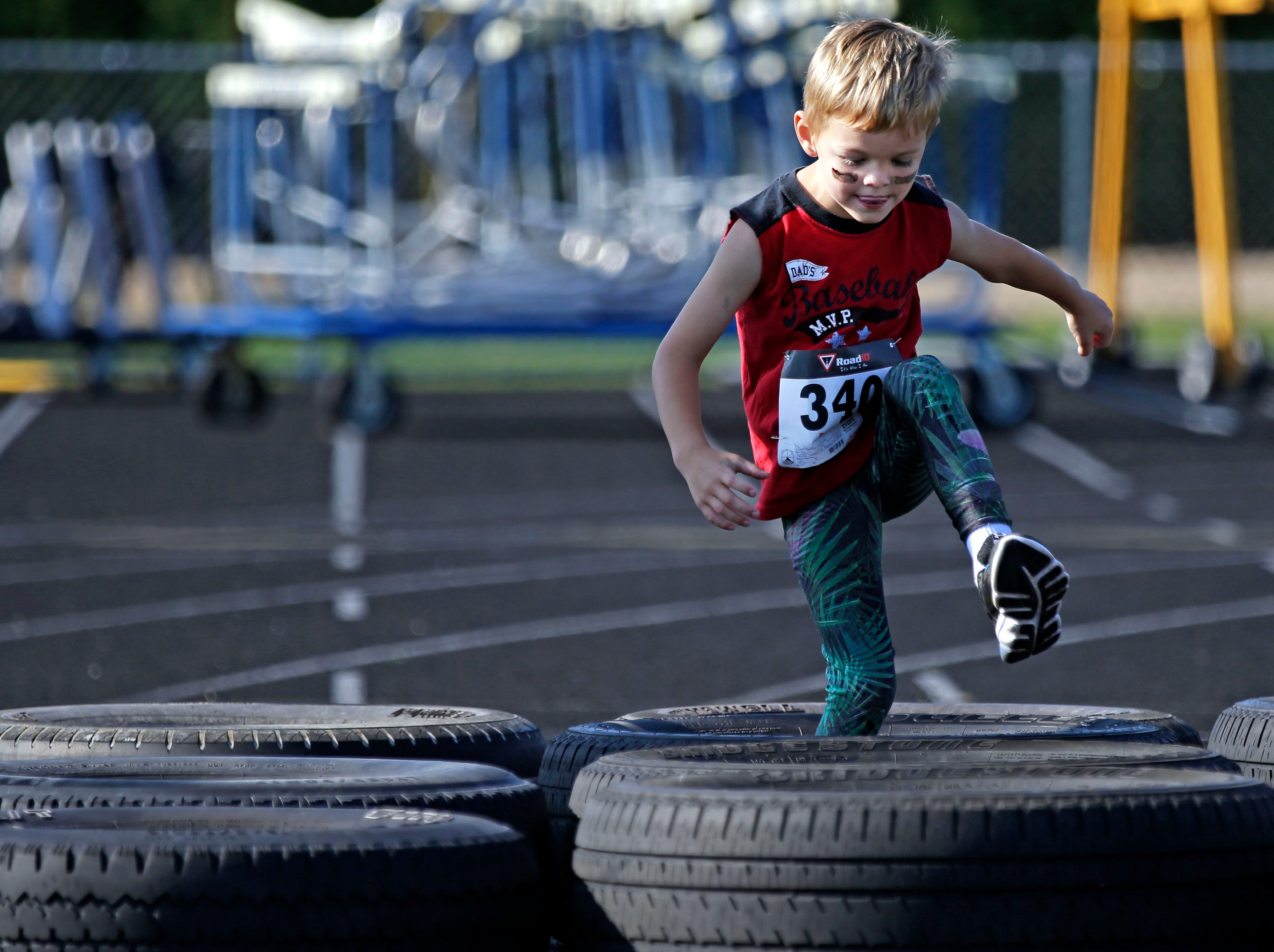Quinn Dunham of Neenah steps through a tire obstacle as Cole's Cancer Crusade, an obstacle course for kids takes place Saturday, July 28, 2018, at Appleton East High School in Appleton, Wis. The event raised funds for the Snowdrop Foundation Wisconsin Chapter.Ron Page/USA TODAY NETWORK-Wisconsin