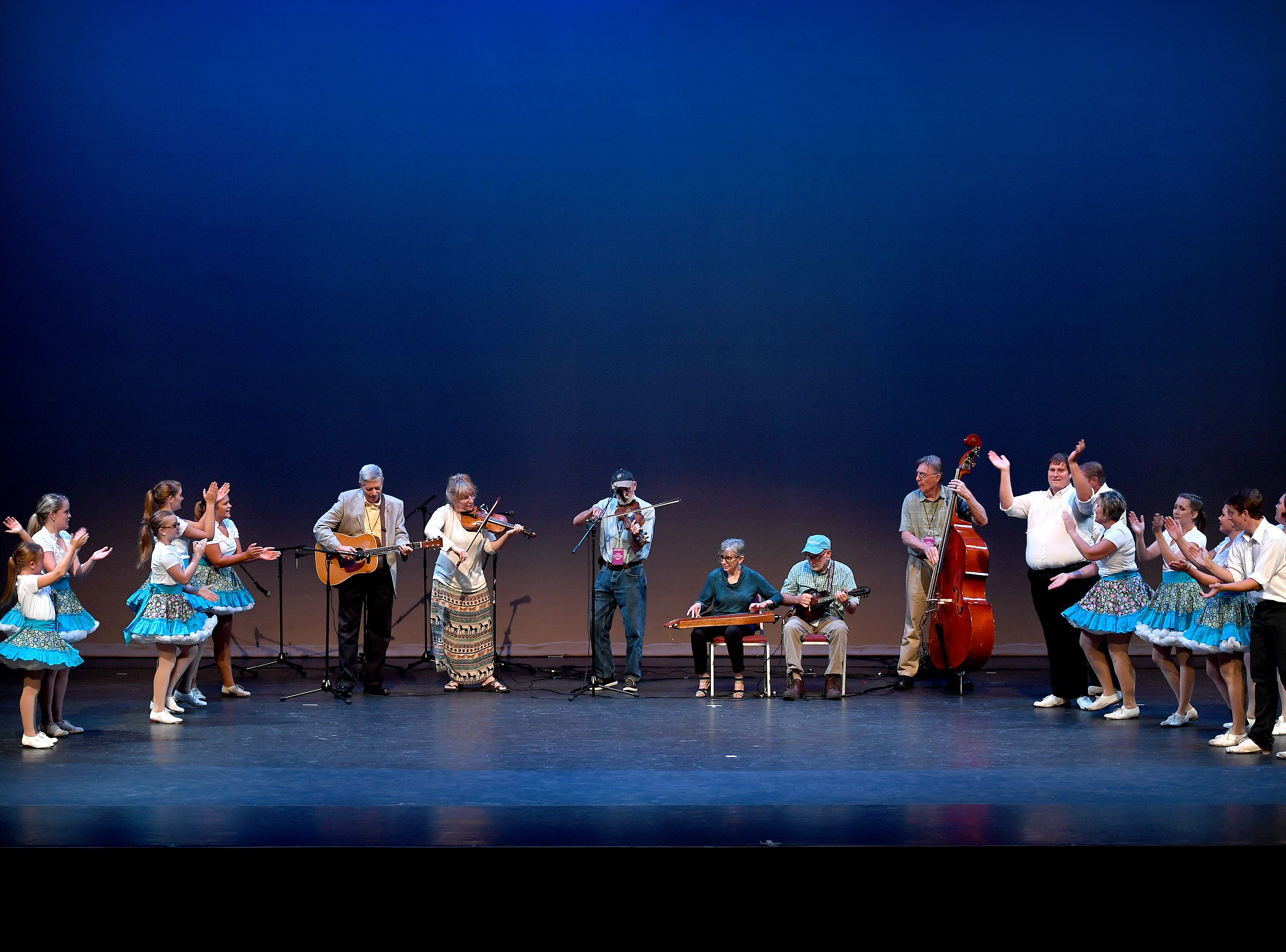 Members of the Hot Foot Cloggers, of Six Mile, South Carolina, give recognition to the Folkmoot band Blackberry Jam who provided music for their performance during a Folkmoot Festival show at the Diana Wortham Theatre on Friday, Aug. 27, 2018.