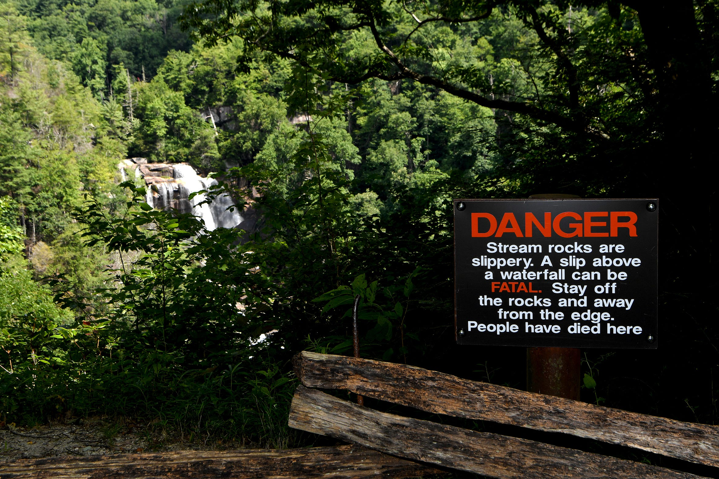 A sign at an observation point uses blunt language at White Water Falls in the Nantahala National Forest on Wednesday, July 25, 2018. The waterfall is the highest in the East at more than 400 feet. It is also one of the most deadly. A least 13 people have died at the falls since 1995.