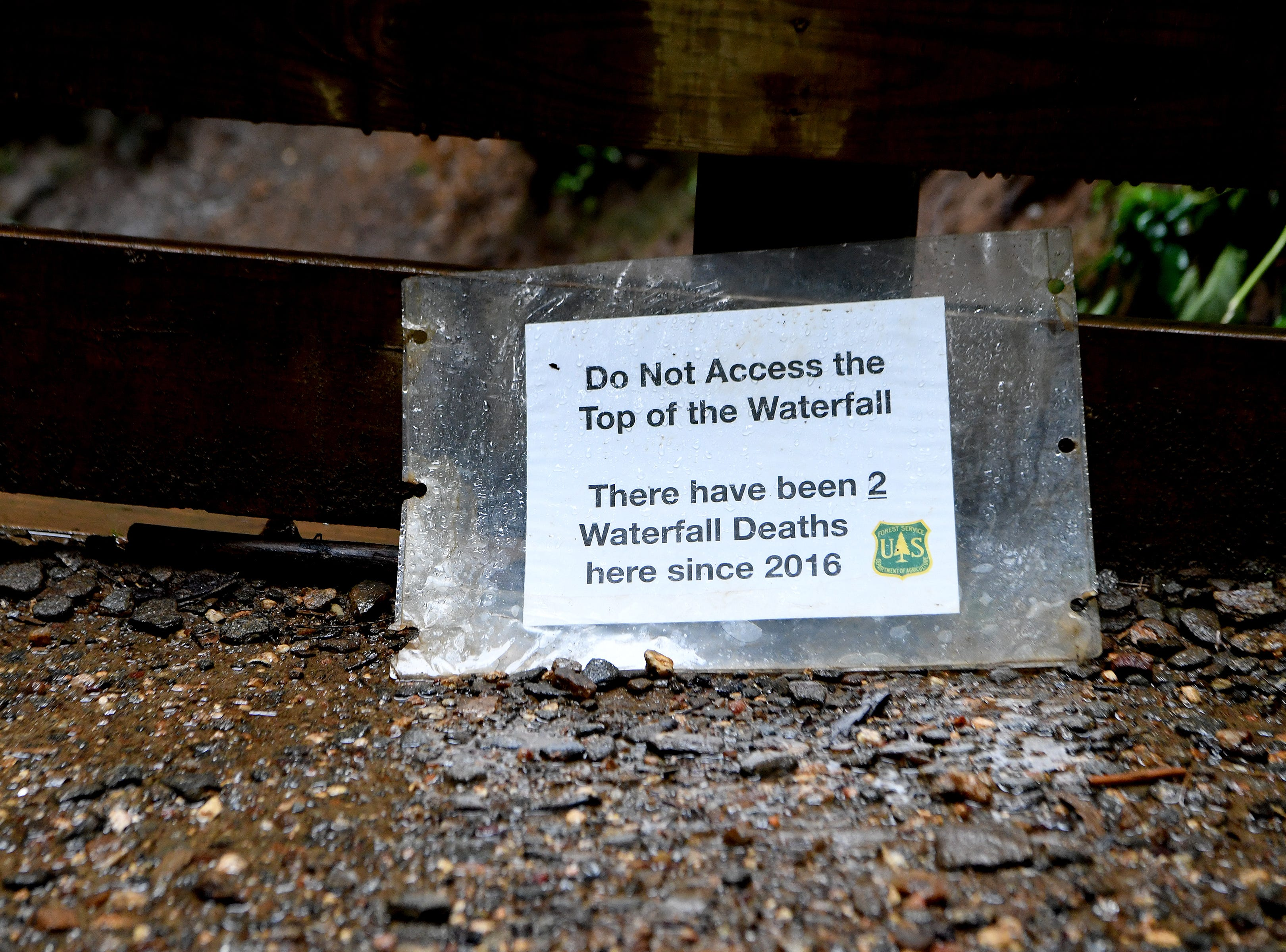 A sign warning against climbing to the top of the waterfall is propped against a railing at Moore Cove Falls in the Pisgah National Forest on Thursday, July 19, 2018. In both 2016 and 2017 a hiker climbed to the top of the waterfall and fell to his death.