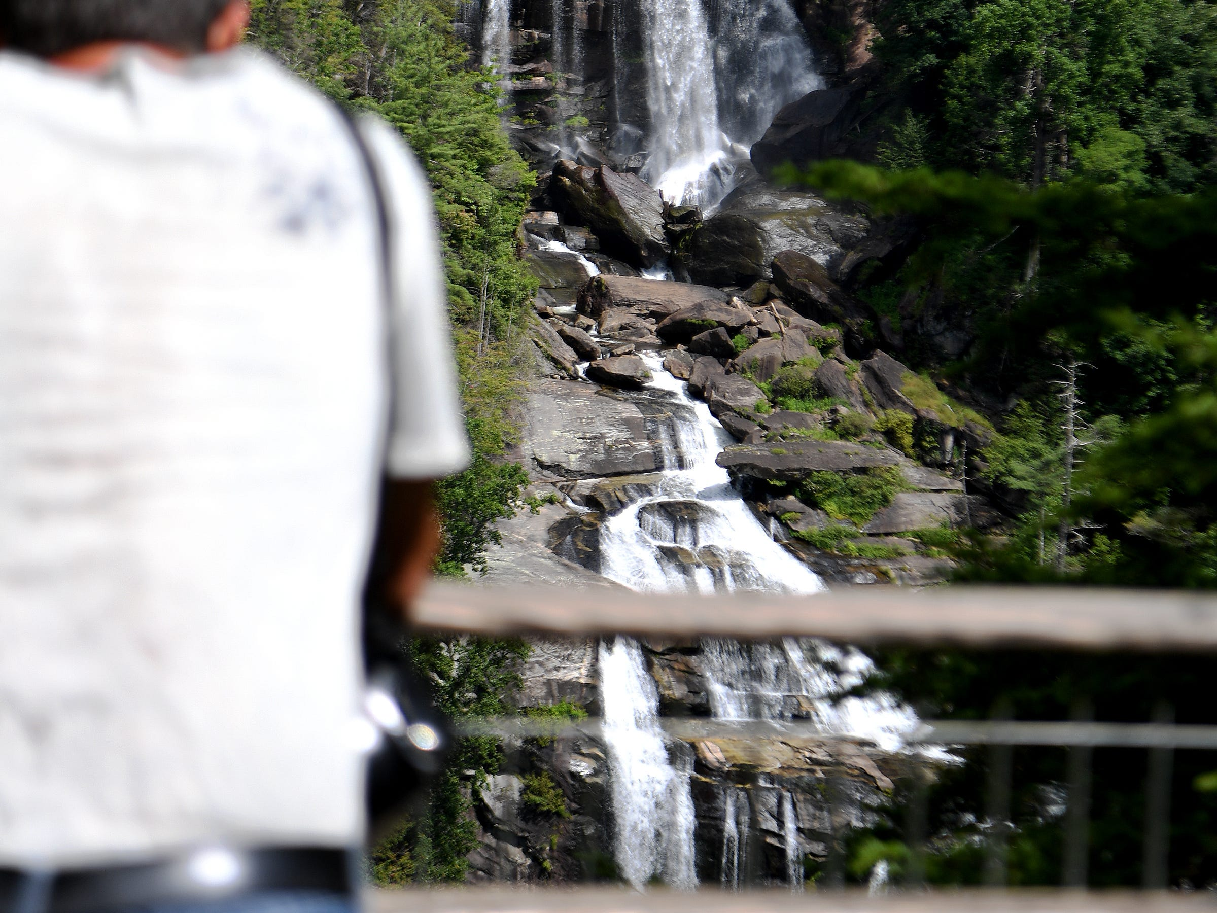 Mike DiLeo, of Murrells Inlet, South Carolina, takes in Whitewater Falls in the Nantahala National Forest from the observation deck on Wednesday, July 25, 2018. The waterfall is the highest in the East at more than 400 feet. It is also one of the most deadly. A least 13 people have died at the falls since 1995.