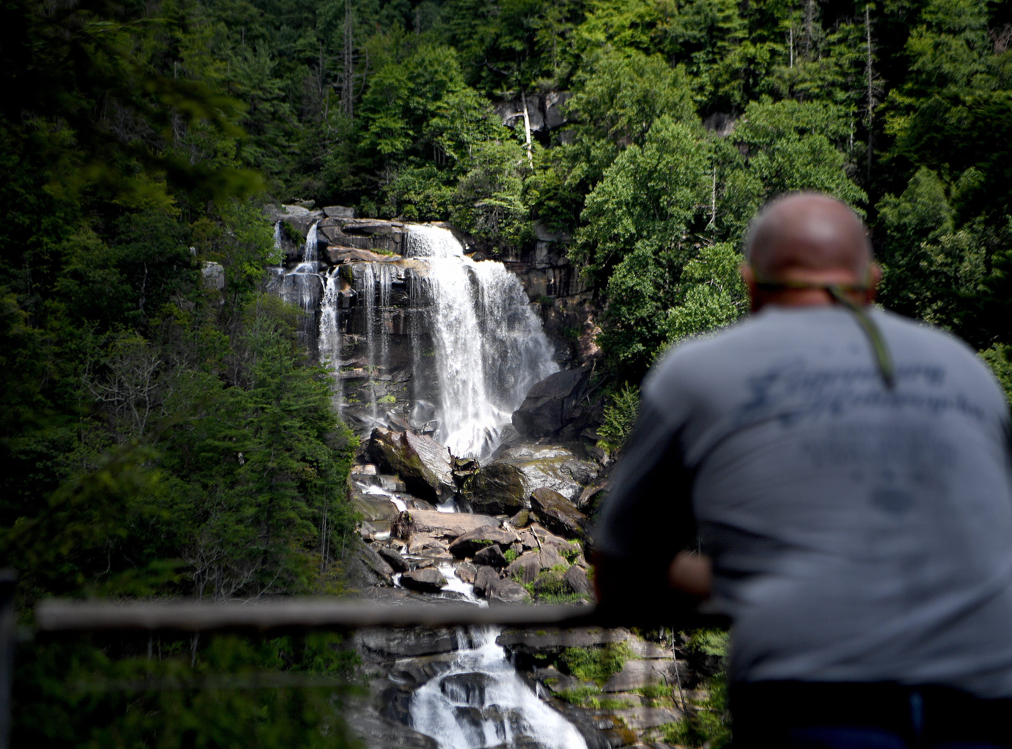 Bille Moore, of Myrtle Beach, South Carolina, takes in Whitewater Falls in the Nantahala National Forest from the observation deck on Wednesday, July 25, 2018. The waterfall is the highest in the East at more than 400 feet. It is also one of the most deadly. A least 13 people have died at the falls since 1995.