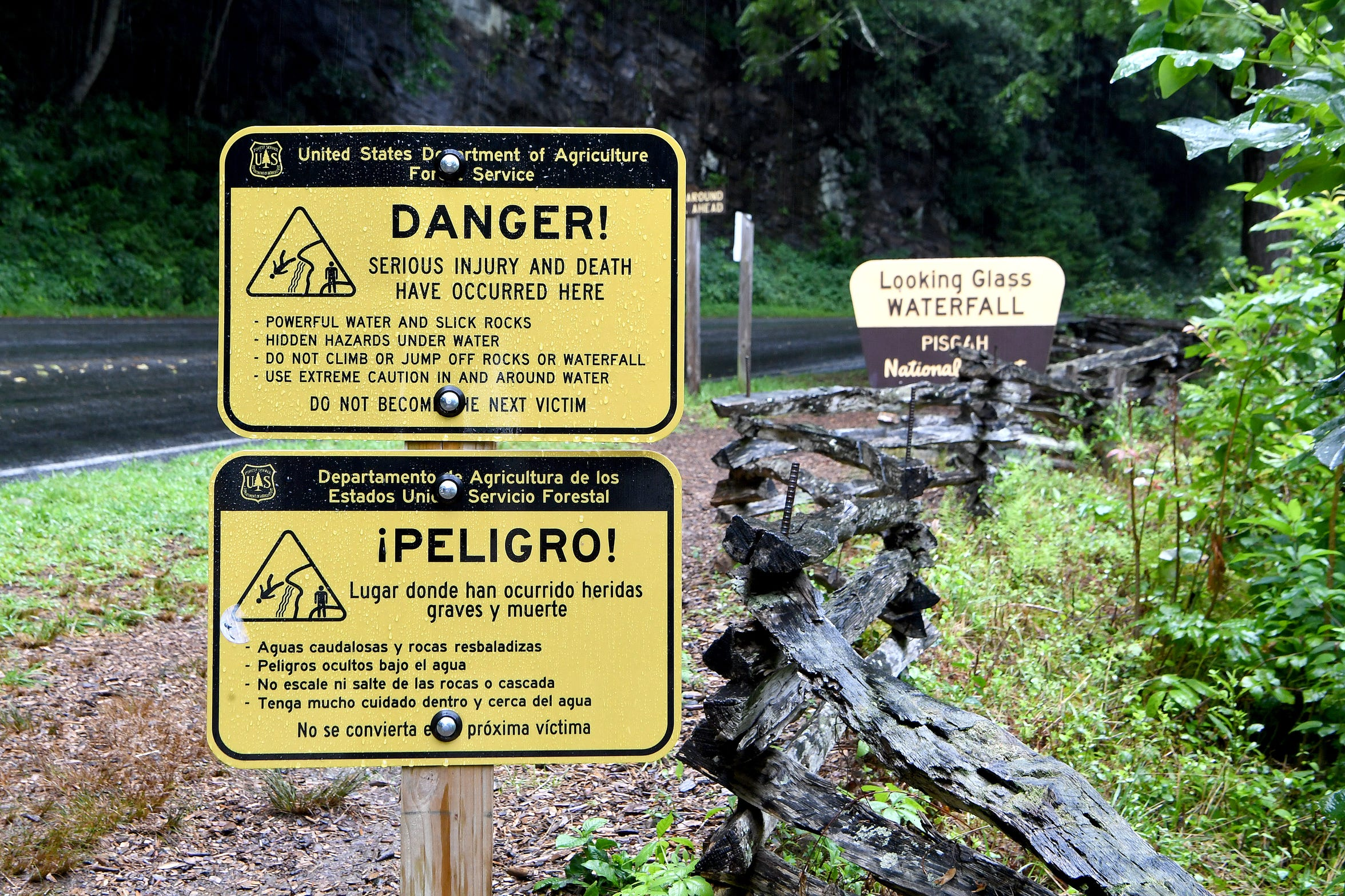 Sign warn of the waterfall's dangers at Looking Glass Falls in the Pisgah National Forest on Thursday, July 19, 2018.