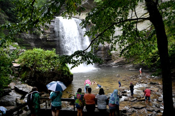 Families play on the rocks and in the water below Looking Glass Falls as others watch from an observation deck on Thursday, July 19, 2018.