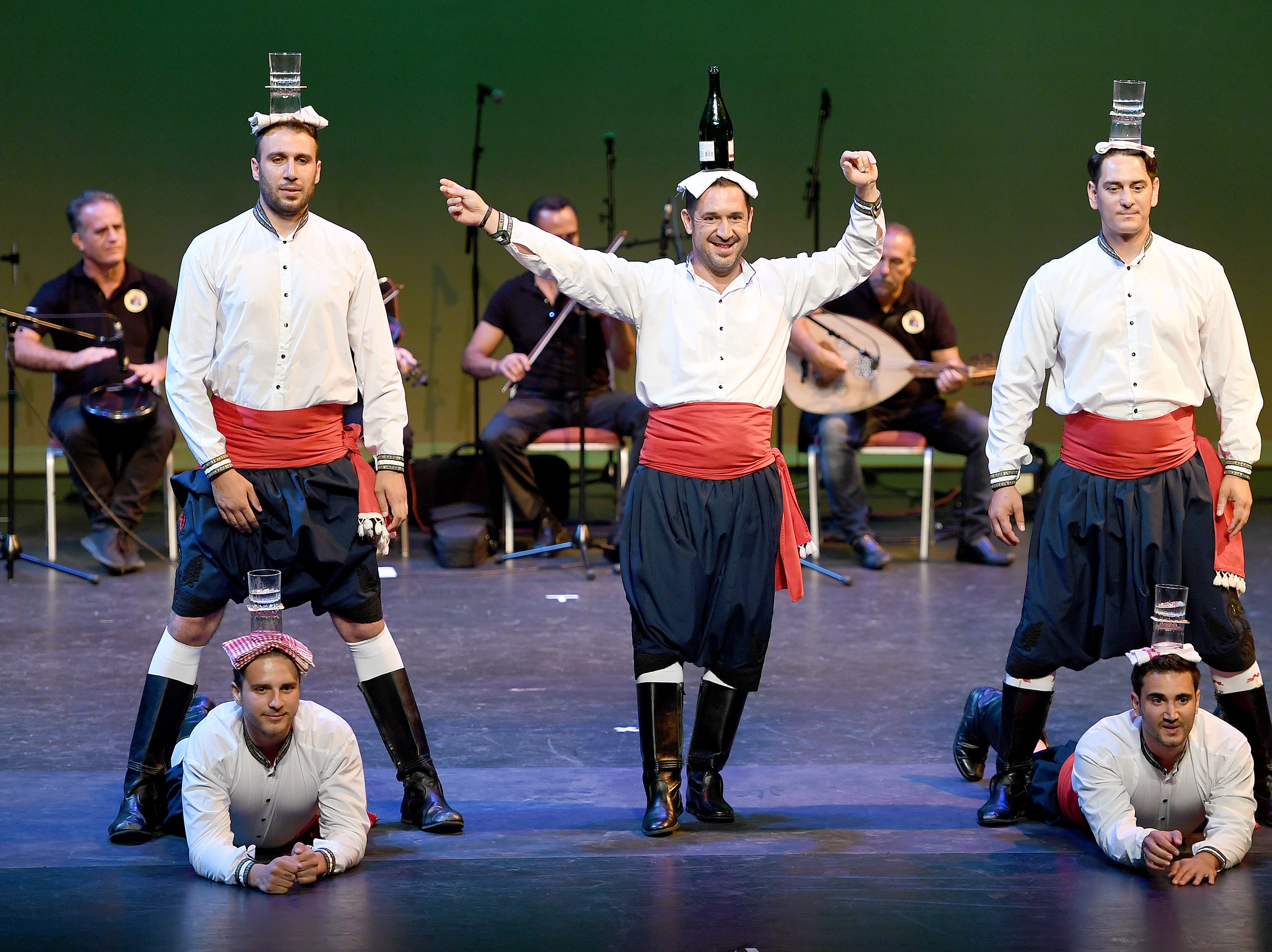 """Members of the Kyrenia Youth Centre Association from Northern Cyprus perform a """"glass dance"""" with water on their heads during a Folkmoot Festival performance at the Diana Wortham Theatre on Friday, Aug. 27, 2018."""