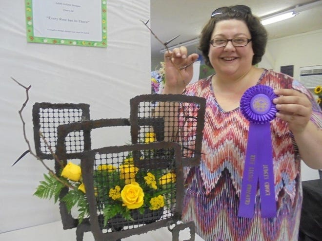 """Amy Vaughn was tickled pink when her floral interpretation of """"Every Rose Has Its Thorn"""" receivedthe flower show judge's choice for distinction in design."""
