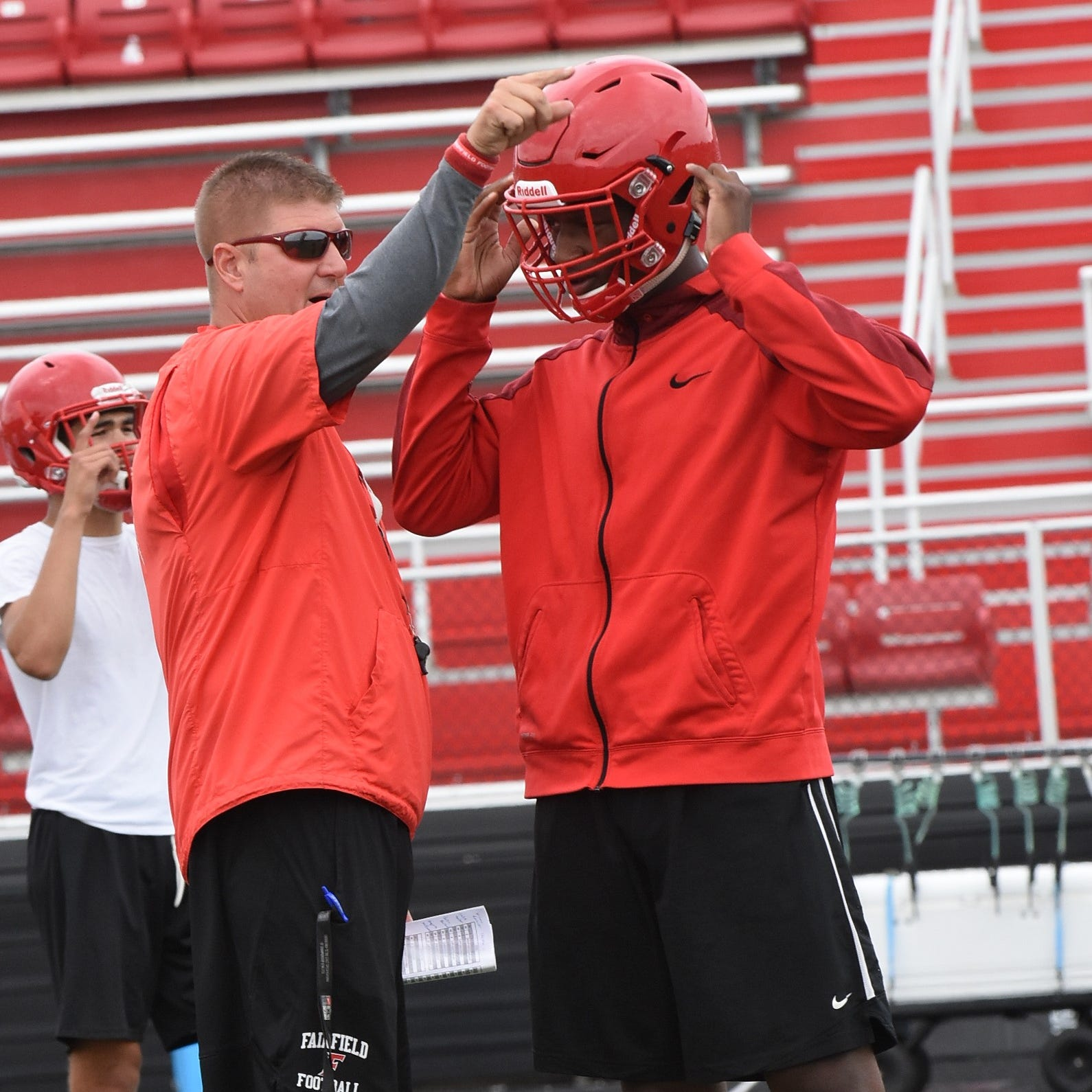 Fairfield Head Football Coach Jason Krause points out directions to his Quarterback Jeff Tyus during morning practice, July 30, 2018.