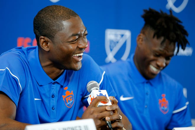 New FC Cincinnati signee Fenando Adi laughs as he answers questions with Fatai Alashe during a press conference.