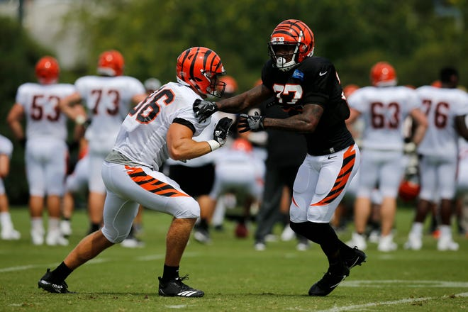 Cincinnati Bengals tight end Mason Schreck (86) and defensive back Tyrice Beverette (37) bump on a play during a camp practice session at the Paul Brown Stadium practice facility in downtown Cincinnati on Monday, July 30, 2018.