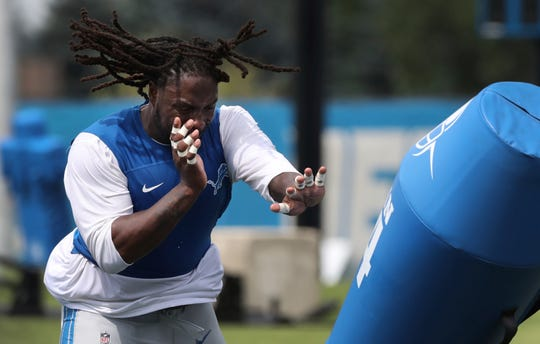 Lions defensive tackle Ricky Jean Francois knocks down a practice dummy during training camp on Monday, July 30, 2018, in Allen Park.