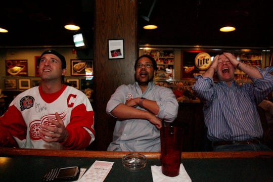 "Red Wings fans (left to right): Max Tressler (cq), 43, of Dearborn, Mich., Miguel Mickey (cq-al), 34, of Novi, Mich., and Scott Alexander (cq-al), 45, of Farmington Hills, Mich., react when the Detroit Red Wings miss a goal during the game against the Edmonton Oilers game at Cobo Joe's Bar & Restaurant in Detroit Sunday, April 23, 2006. ""I think it sucks that we're losing,"" said Alexander."