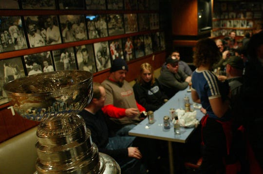 Patrons line up to have their moment with the Stanley Cup at the Lindell AC in Detroit on Dec. 8, 2002.