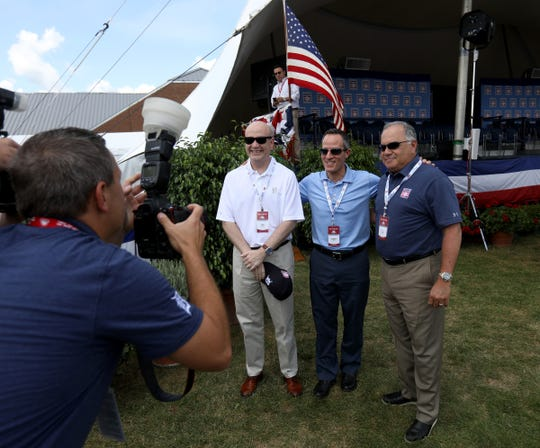 A Detroit Tigers photographer takes pictures of Ilitch Holdings Inc. Group President Chris Granger, Detroit Tigers owner Chris Ilitch and Detroit Tigers general manager Al Avila before the start of the Baseball Hall of Fame induction ceremony at the Clark Sports Center in Cooperstown, N.Y. on Sunday, July 29, 2018.