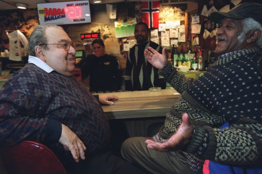 Lindell AC owner Johnny Butsikaris left, chats with a long-time patron on Dec. 3, 2002, five days before the bar was set to close.