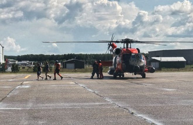 Survivors from a plane crash on North Fox Island disembark a Coast Guard Air Station Traverse City MH-60 Jayhawk helicopter in Traverse City.